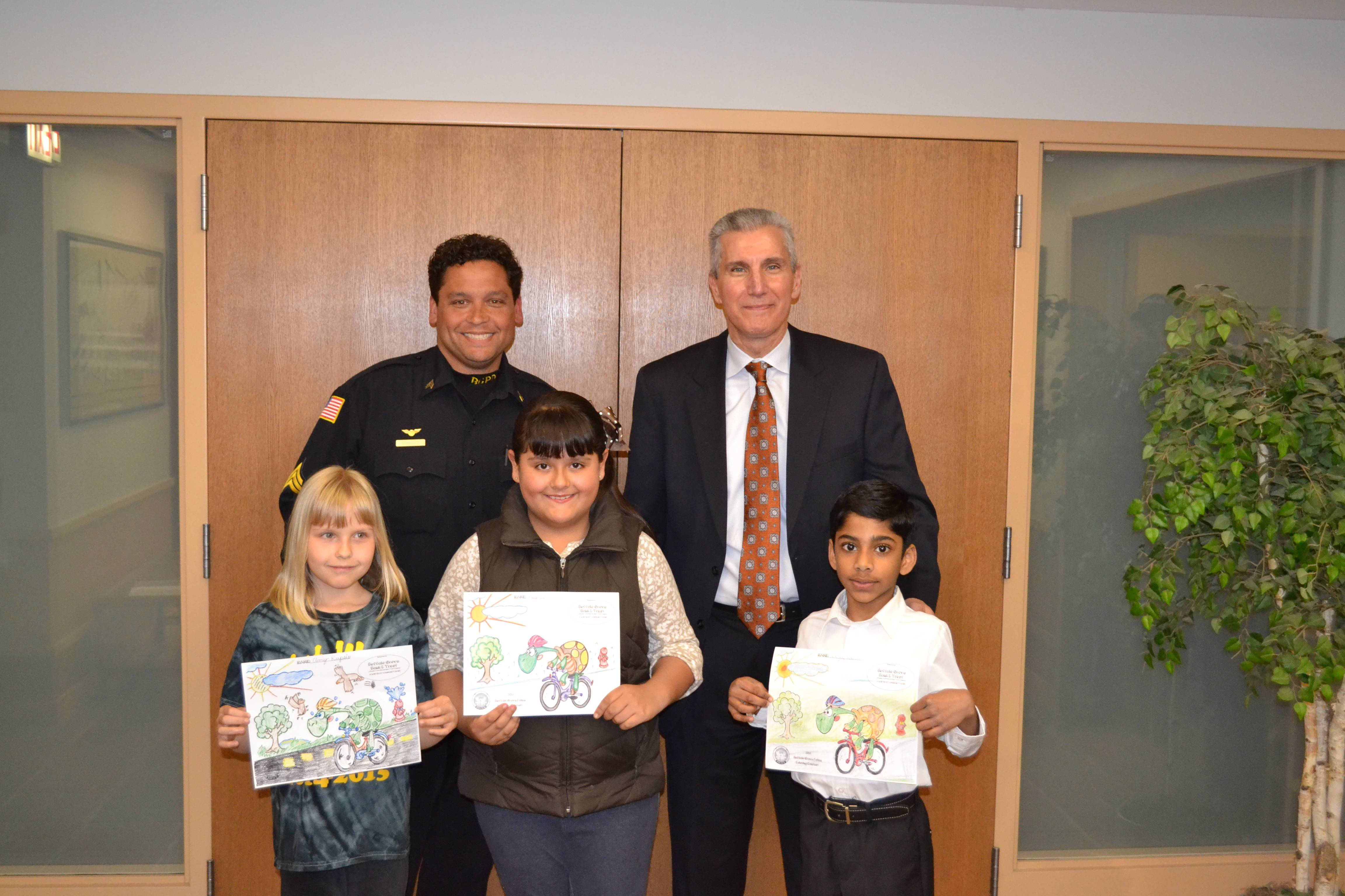 Winners of the coloring contest include, from left, Amy Rupsis, third grade, St. Mary's School; Regina Garcia, second grade, Tripp Elementary School; and Nagayuvan Ayyachamy, first grade, Tripp Elementary School. In back are Buffalo Grove Police Officer Michael Rodriguez and Mike Abruzzini from the Buffalo Grove Bank & Trust.