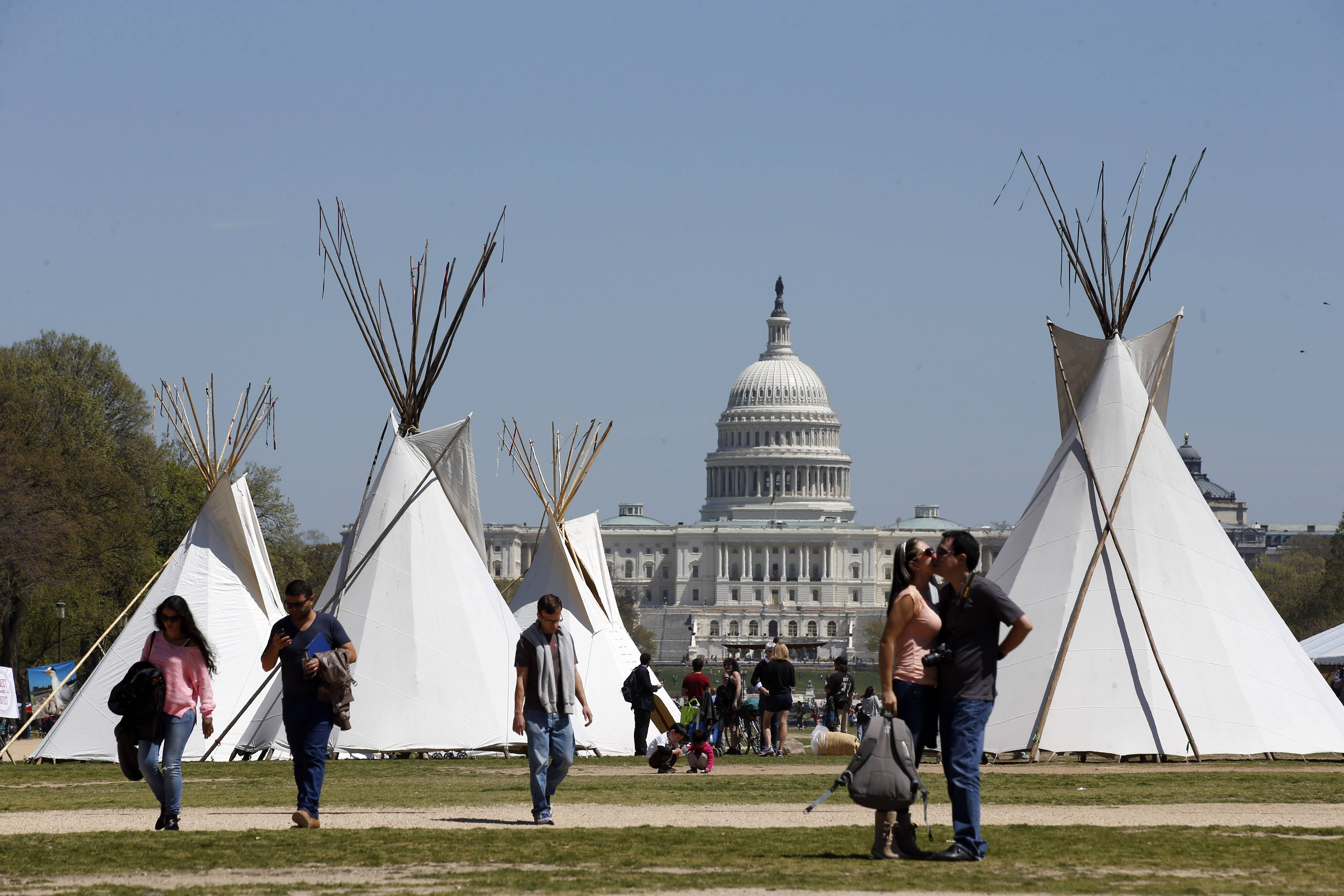 People walk near teepees set up on the National Mall in Washington, looking toward the Capitol. Days after President Barack Obama touted executive actions aimed at increasing energy efficiency, a bill with similar goals is expected to fall victim to partisan gridlock in the Senate. A bipartisan bill to promote many of the same efficiency goals Obama touted May 9 in California is expected to go down in defeat May 12 amid a dispute over the Keystone XL oil pipeline.