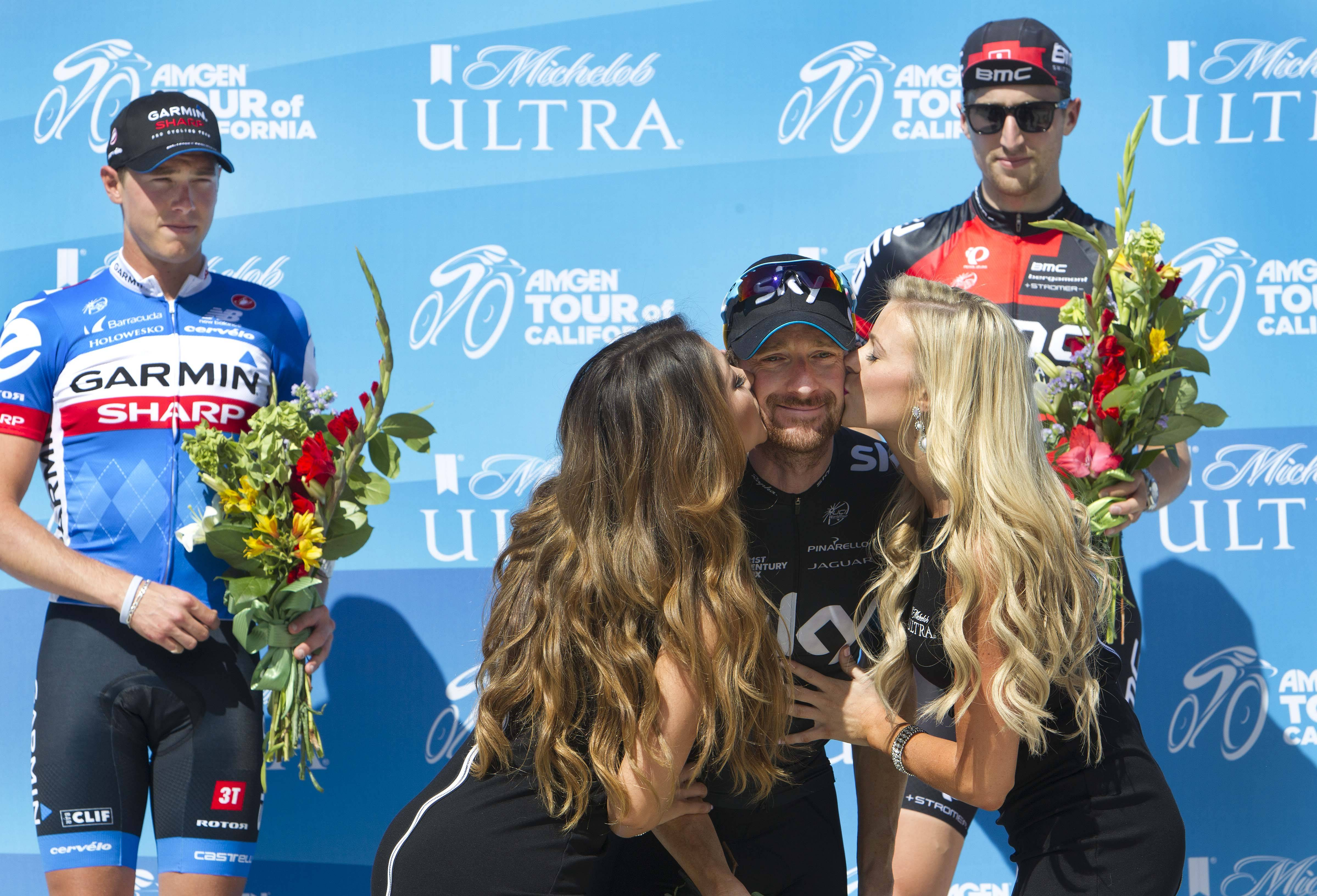 Bradley Wiggins of Team SKY, center, accepts kisses during the podium ceremony Monday after winning the second stage of the Amgen Tour of California in Folsom.