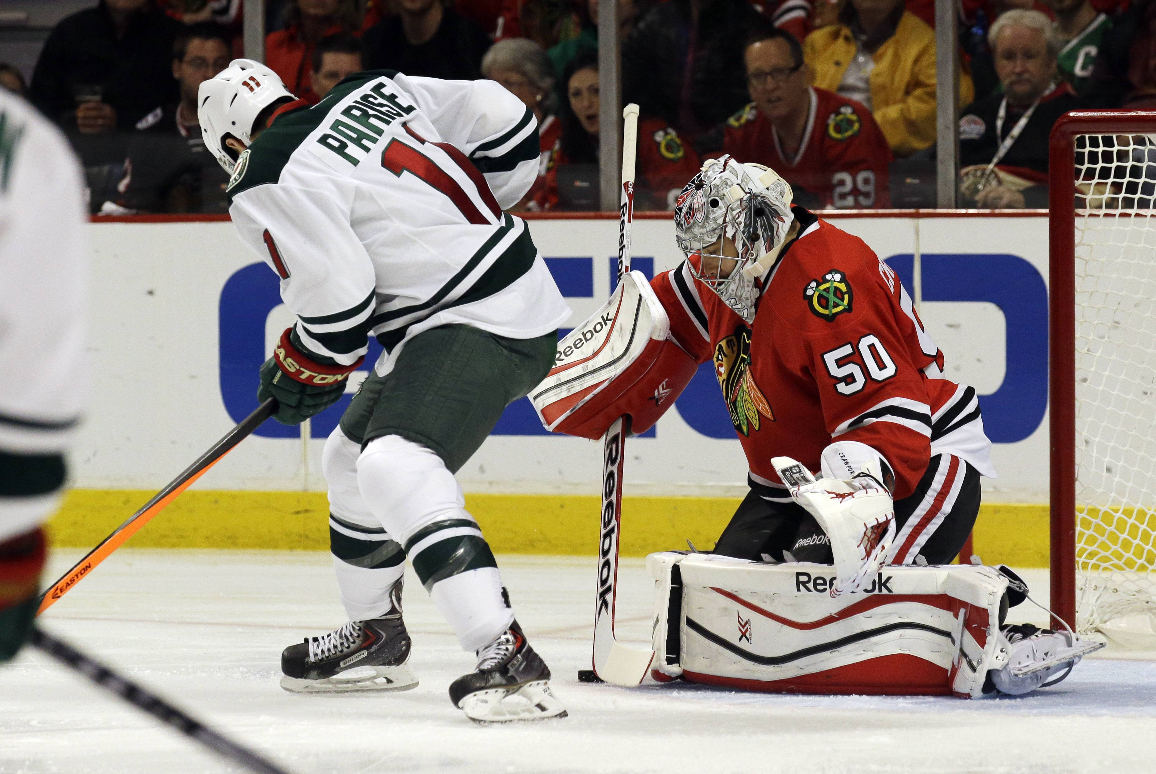 Hawks goalie Corey Crawford blocks a shot by the Wild's Zach Parise during second-round playoff action.