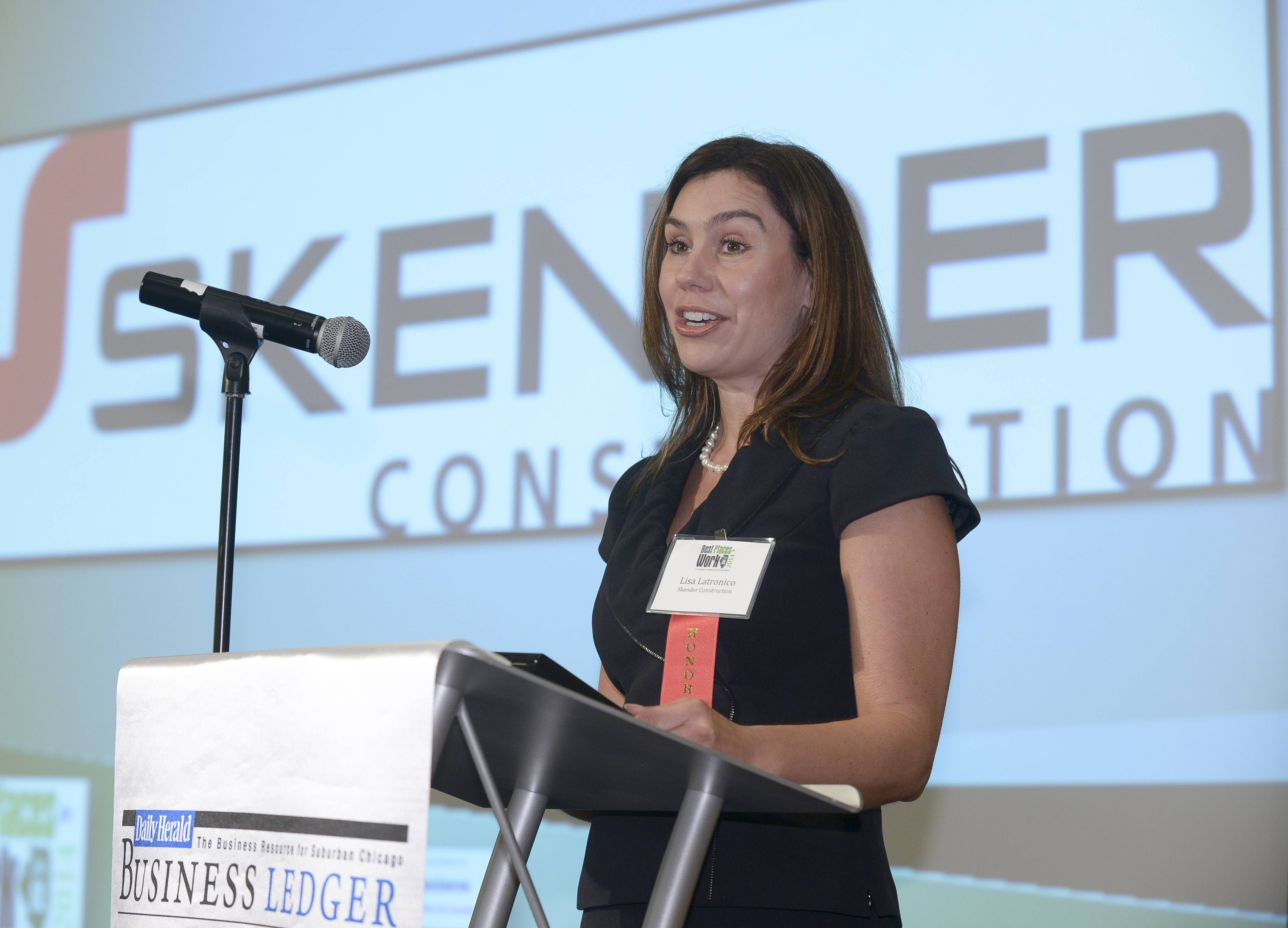 Lisa Latronico, director of human resources for Skender Construction of Chicago, accepts the first-place award for the Daily Herald Business Ledger's Best Places to Work in Illinois 2014 for medium-sized employers during a ceremony at the Chicago Marriott Oak Brook.