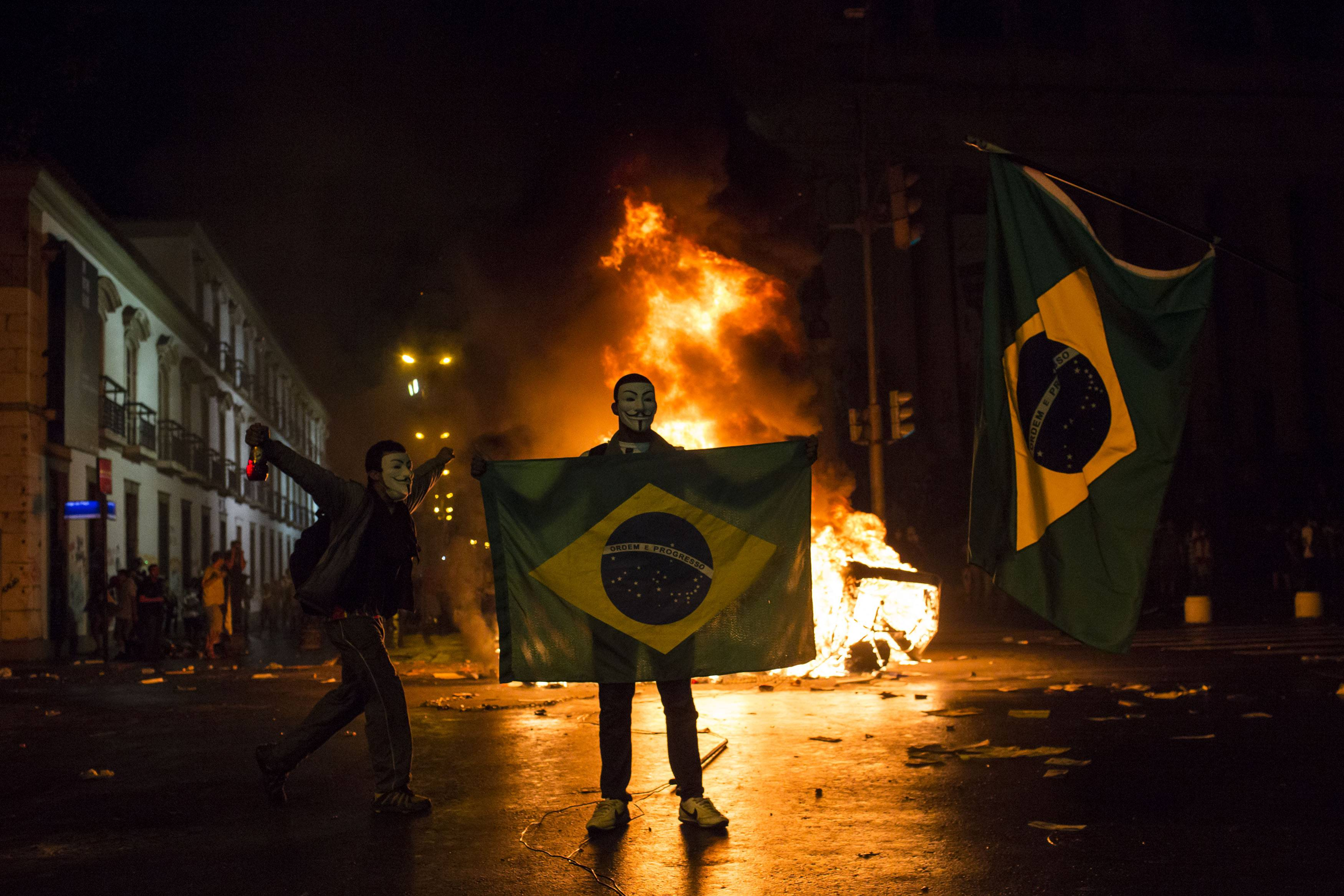 A demonstrator holds a Brazilian flag in front of a burning barricade during a protest in Rio de Janeiro. Brazil. In a poll last year, more than three-fourths of Brazilians said they're certain corruption has infused the World Cup. Their anger fueled widespread and often violent anti-government protests last June that sent more than 1 million Brazilians into the street during FIFA's Confederations Cup soccer tournament.