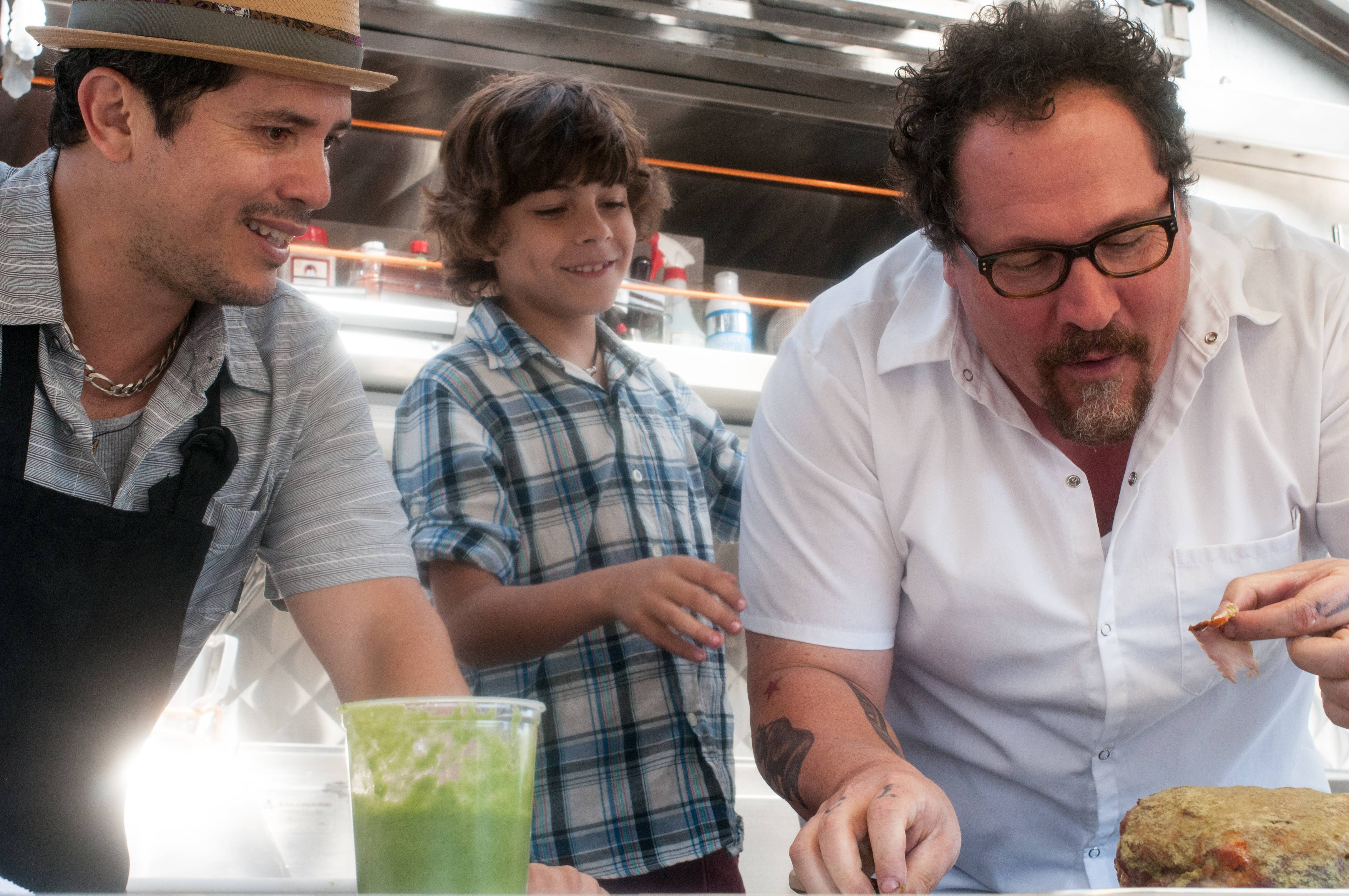 "John Leguizamo, left, Emjay Anthony and Jon Favreau star as food truck cuisine specialists in ""Chef."""