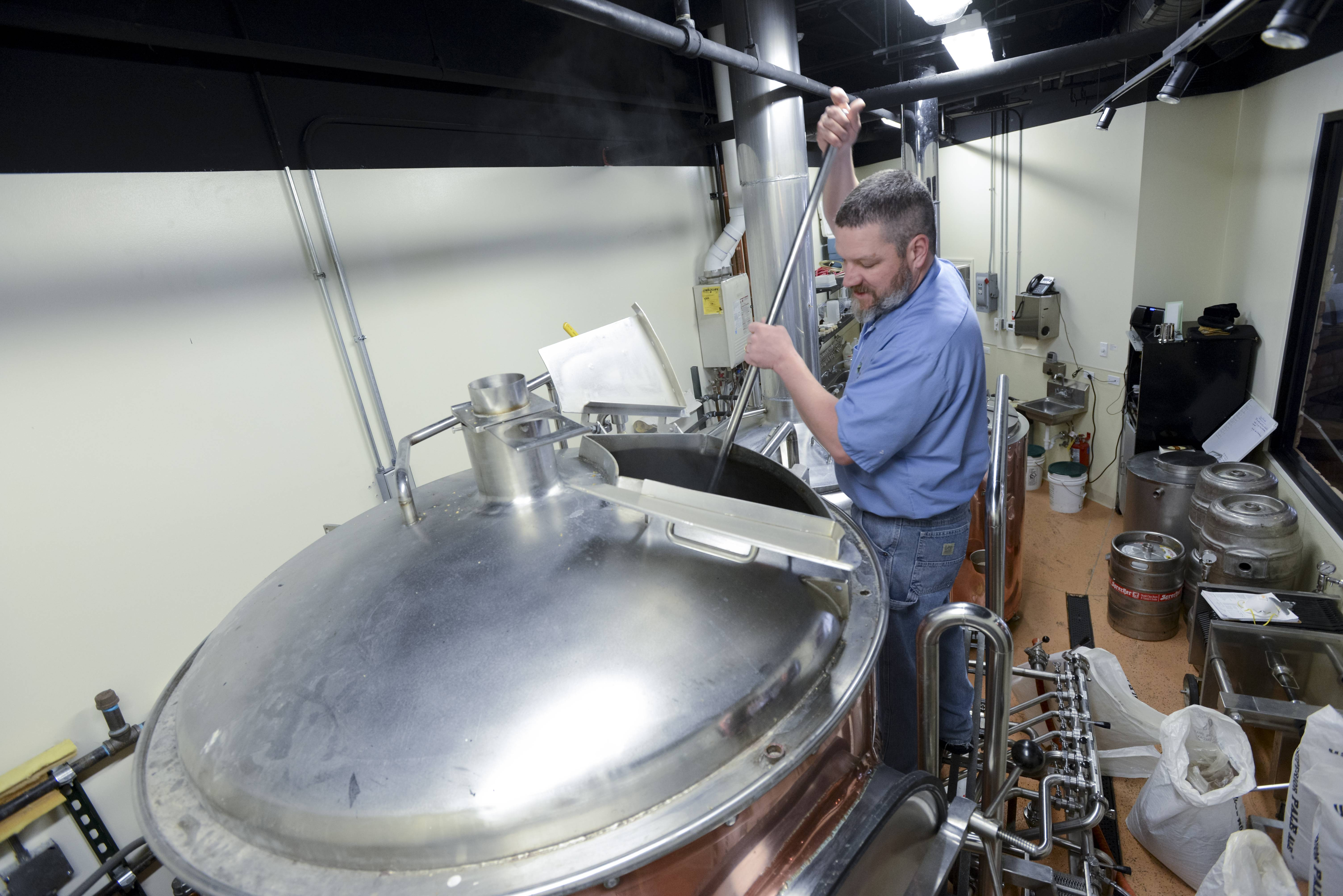 Brewmaster Ken McMullen stirs the mash as he brews up a batch of IBA, India Brown Ale, at the Hopvine Brewing Company in Aurora.