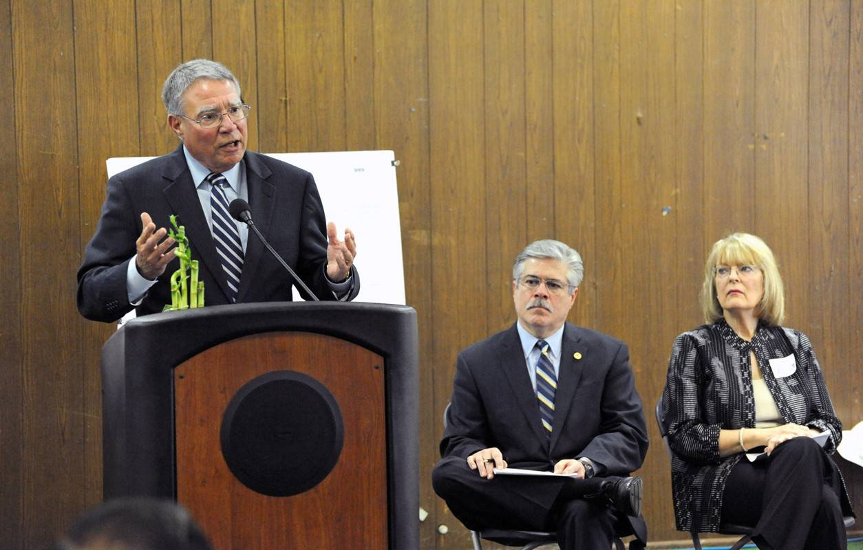 Harper College President Ken Ender speaks at a ceremony marking the start of construction on the Hanover Park Education and Work Center as state Rep. Fred Crespo and Harper Board Chair Diane Hill look on.
