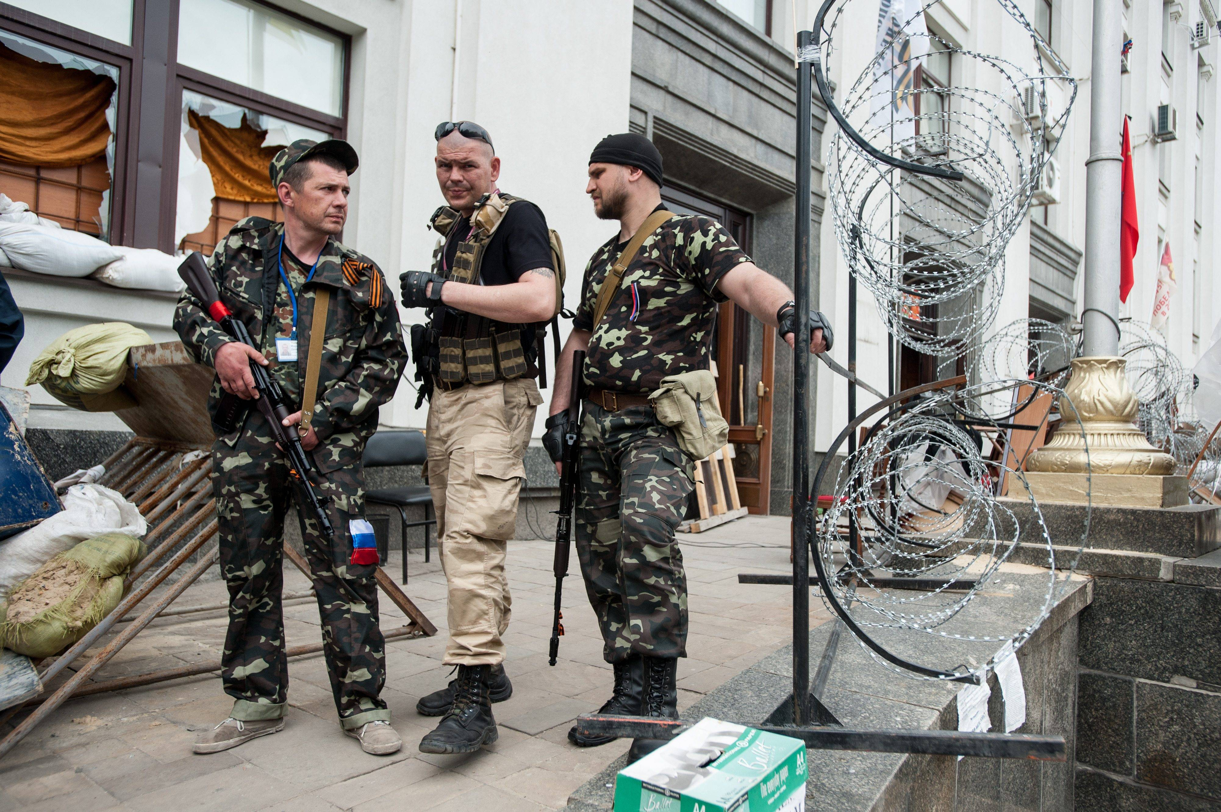 Pro-Russian armed men stand at the city hall in the eastern Ukraine city of Luhansk on Monday.