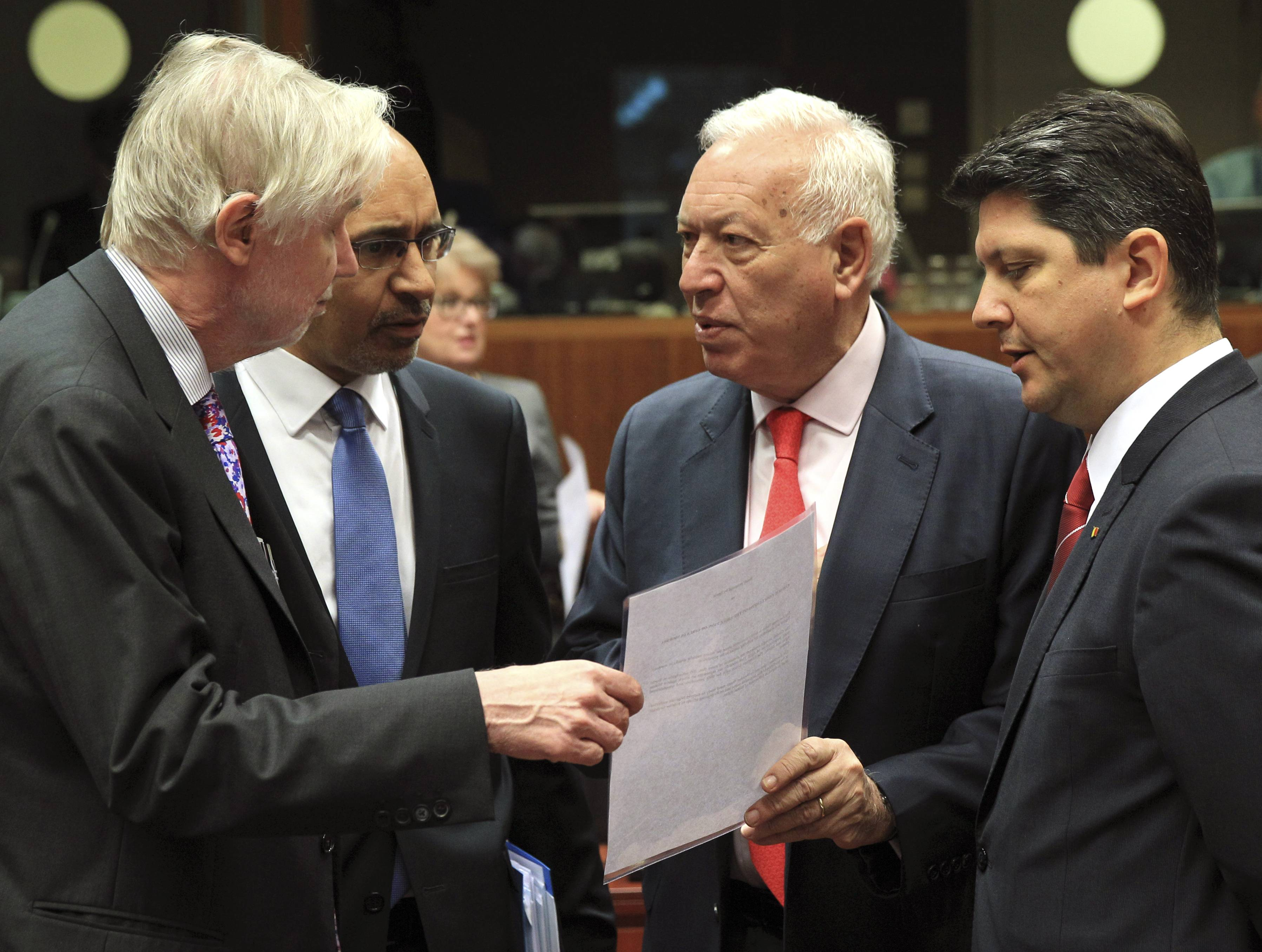 Spain's Foreign Minister Jose Manuel Garcia-Margallo y Marfil, second right, talks with Finland's Foreign Minister Erkki Sakari Tuomioja, left, French Secretary of State for European Affairs Harlem Desir, second left, and Romania's Foreign Minister Titus Corlatean during an EU foreign ministers meeting at the European Council building in Brussels Monday.