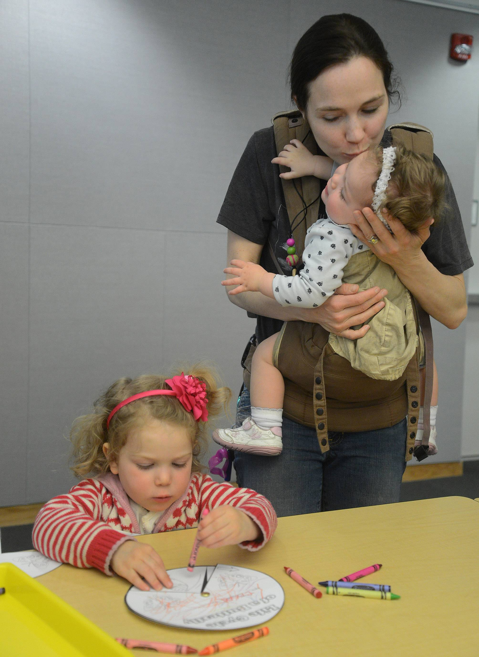 Holly Aronoff, of Vernon Hills, holds one-year-old Violet, while helping her three-year-old Celia color butterflies, during the Vernon Area Public Library Preschool Science Detectives program.