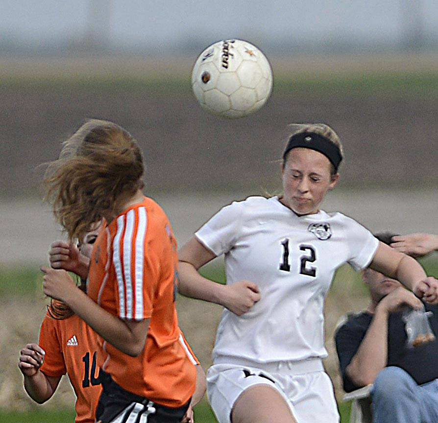 Kaneland's Madison Jercenko, right, goes for a header Monday against DeKalb in Maple Park.