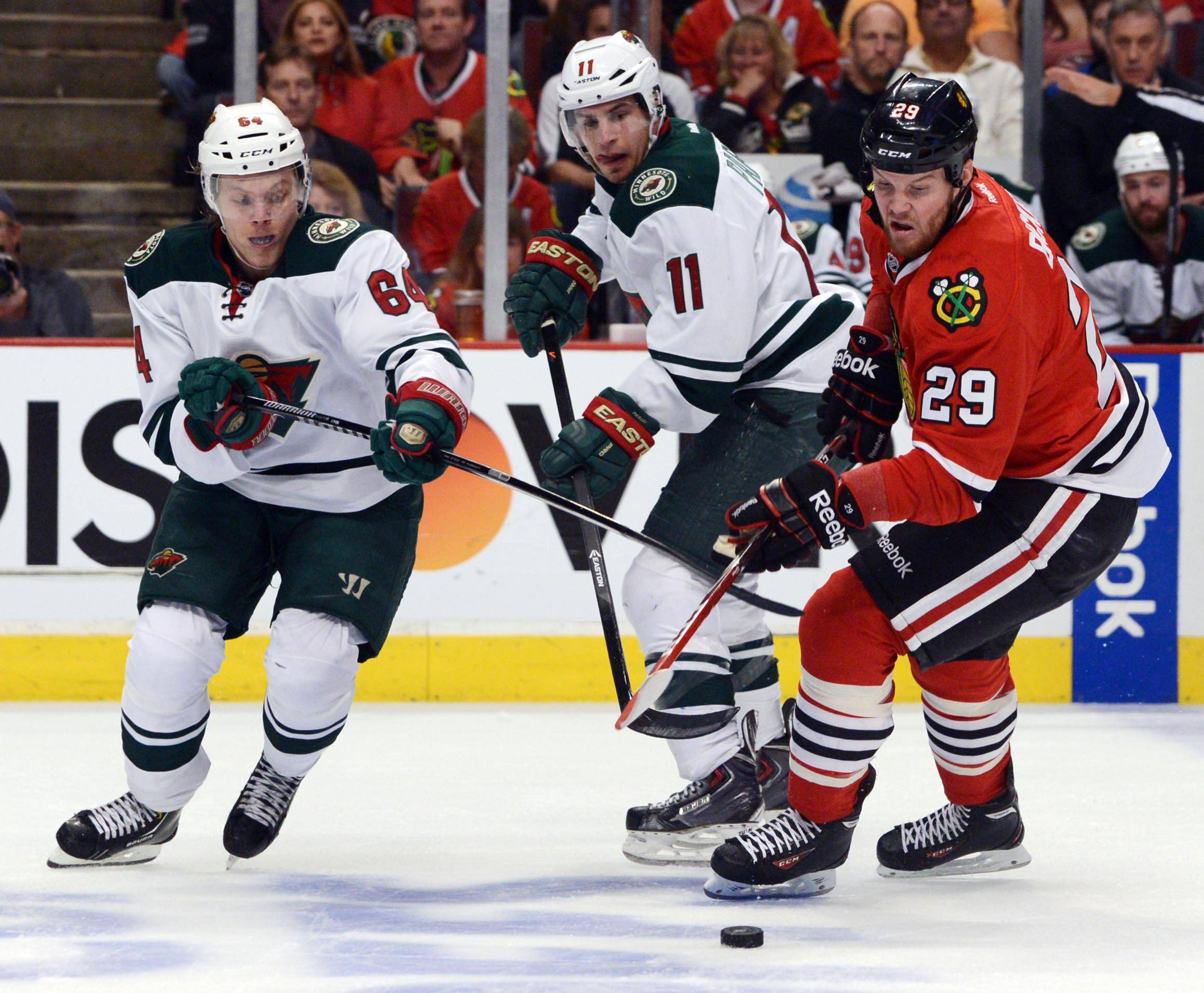 Chicago Blackhawks left wing Bryan Bickell fights for the puck against Minnesota Wild center Mikael Granlund and left wing Zach Parise Sunday in Game 5 of round 2 of the Stanley Cup Playoffs at the United Center in Chicago.