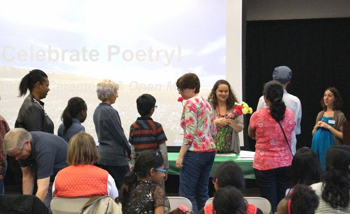 Palatine Library staff hand out carnations to Poetry Contest participants at the awards ceremony on May 3.