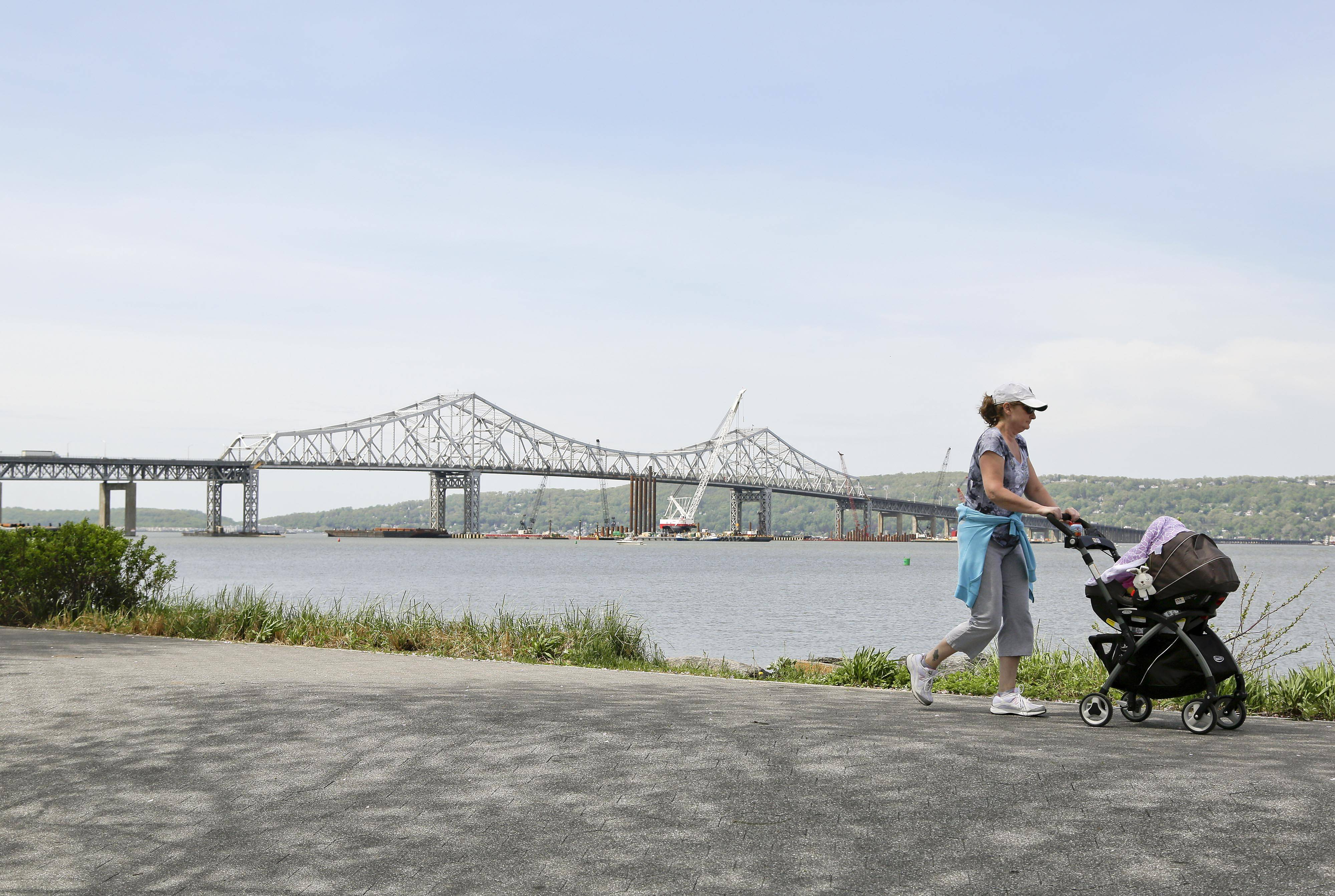 A woman takes a stroll with her child along the Westchester Riverwalk just north of the Tappan Zee Bridge in Tarrytown, N.Y. On Wednesday, President Barack Obama plans to speak by the bridge just north of New York City to press his case that a key federal government fund used to pay for the nation's roads, bridges and ports is running dry and that the economy would be damaged if it is not replenished.
