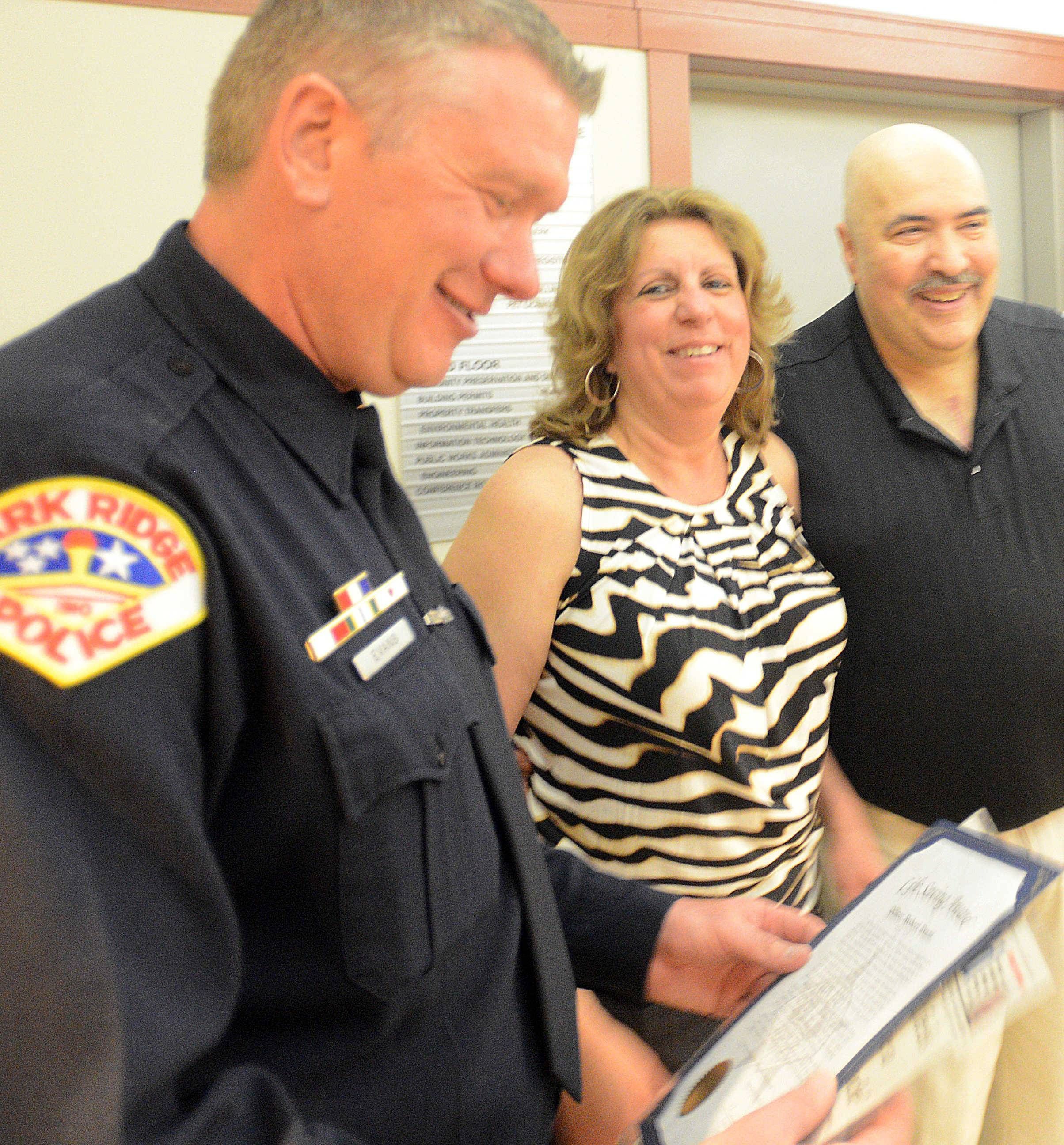 Park Ridge police Officer Robert Evans, left, looks at a certificate of recognition as he shares a laugh with Vita and Jim Maglieri of Mount Prospect on Monday night. Evans was one of several first responders and ordinary citizens honored Monday for helping to save Jim Maglieri's life after he suffered a heart attack March 20 while driving through Park Ridge.
