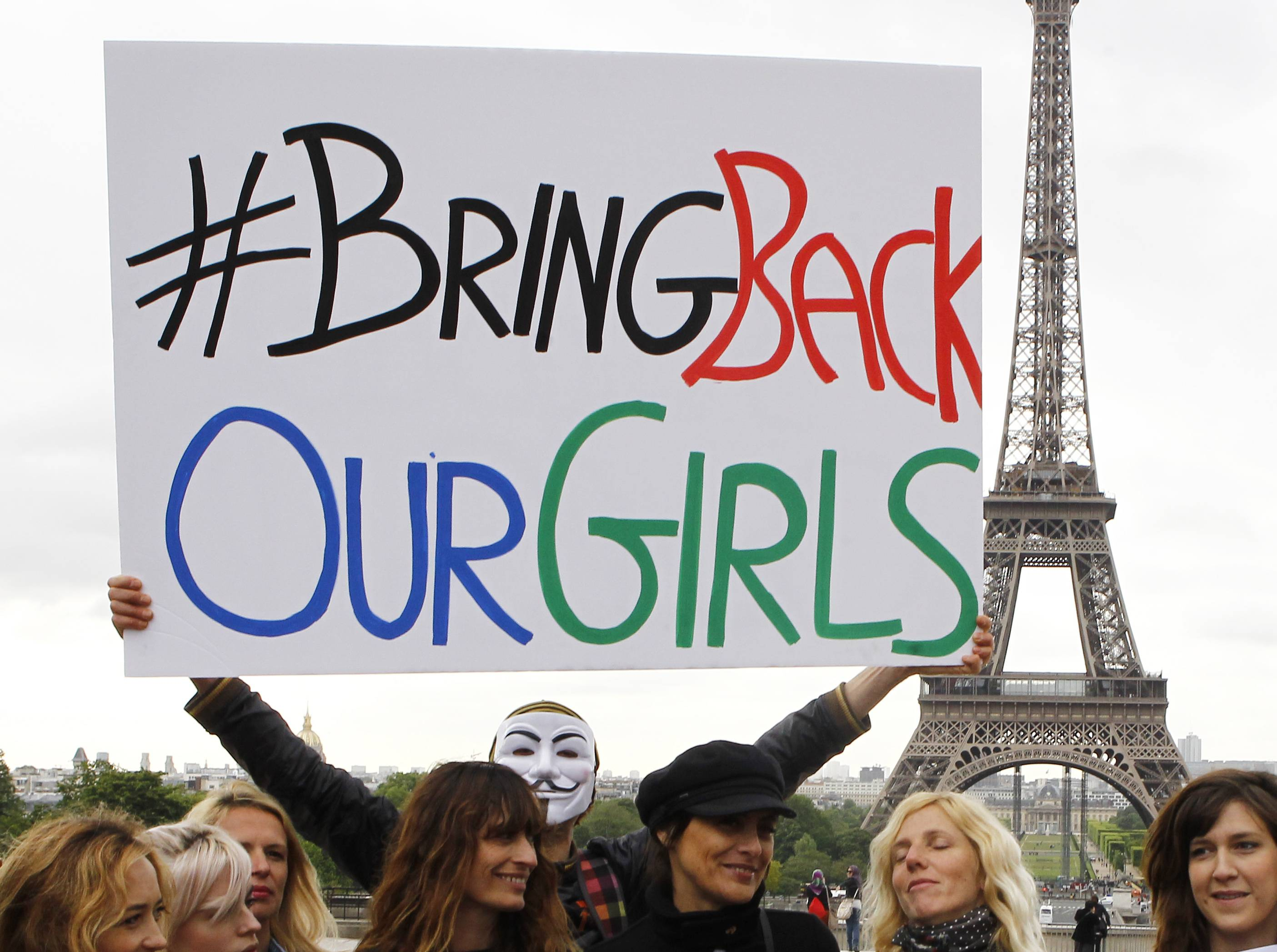 A person holds a poster during a rally at the Trocadero, in front of the Eiffel Tower, to support the release of the kidnapped girls in Nigeria, Tuesday in Paris.