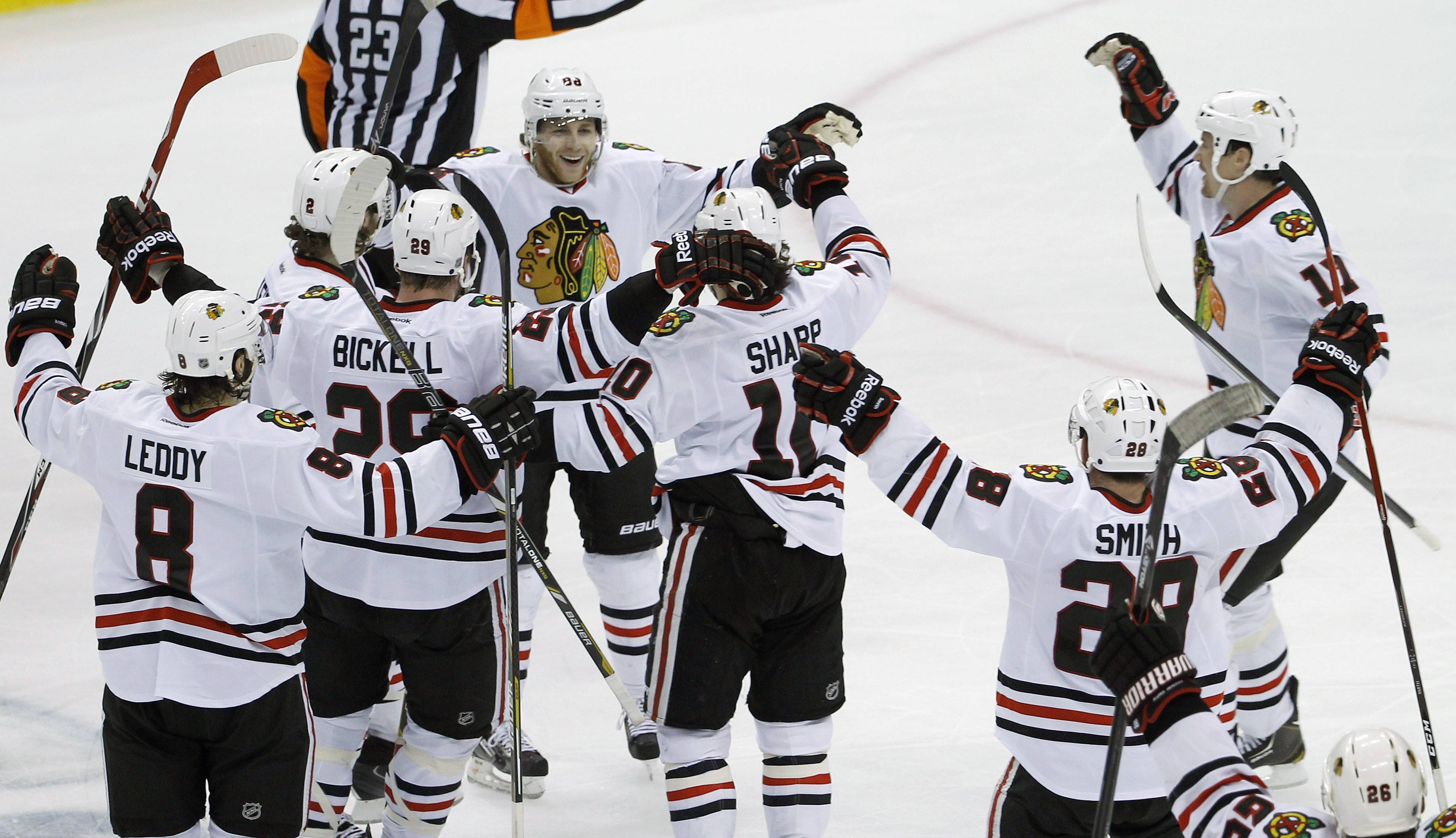 Teamamtes swarm Blackhawks right wing Patrick Kane, center, Tuesday to celebrate his game-winning goal off Minnesota Wild goalie Ilya Bryzgalov to beat the Wild 2-1 during overtime of Game 6 in St. Paul, Minn.