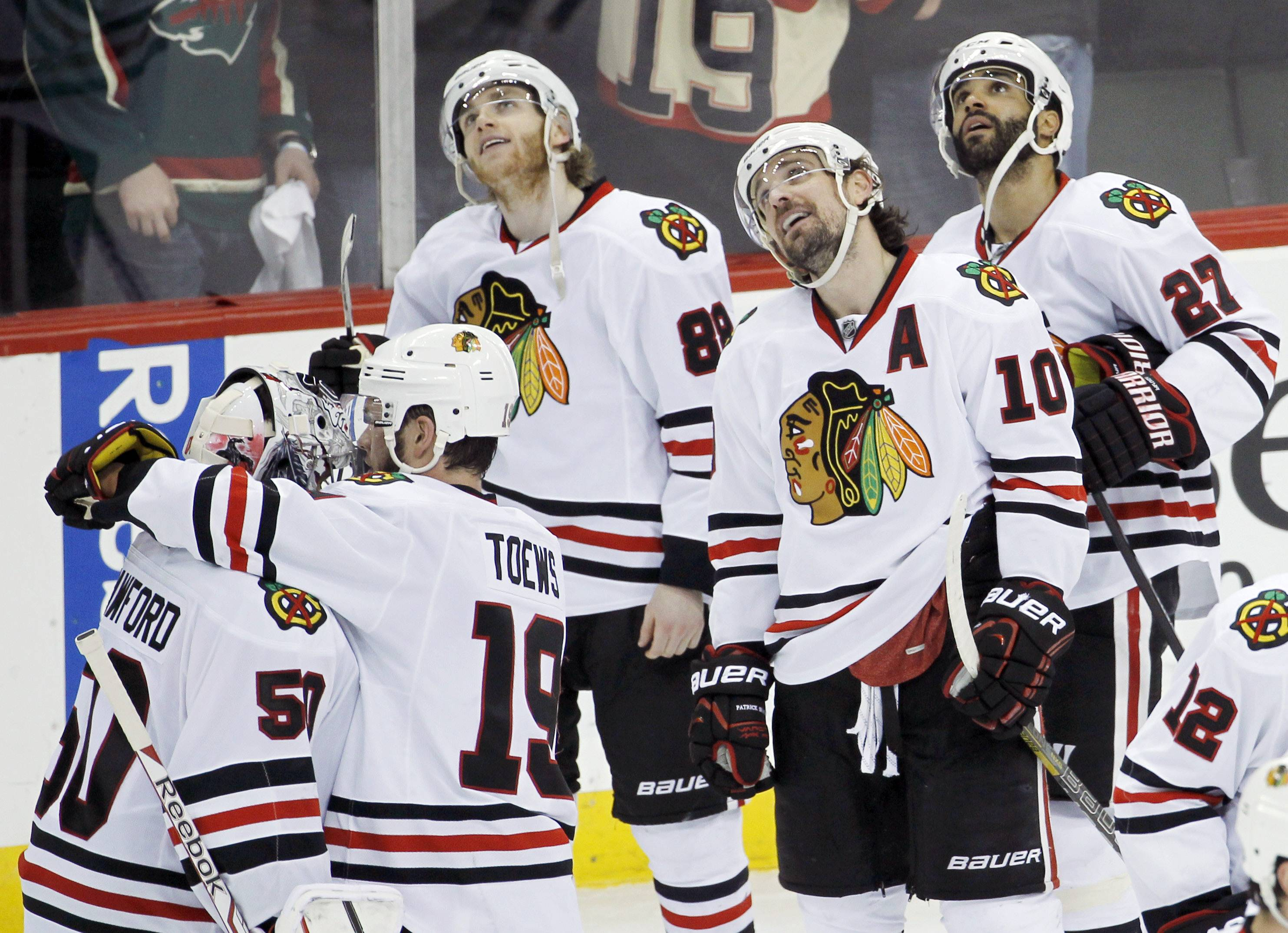 Chicago Blackhawks right wing Patrick Kane, left wing Patrick Sharp (10) and defenseman Johnny Oduya (27) watch the replay of Kane's game-winning goal on Minnesota Wild goalie Ilya Bryzgalov as Blackhawks center Jonathan Toews (19) greets goalie Corey Crawford (50).