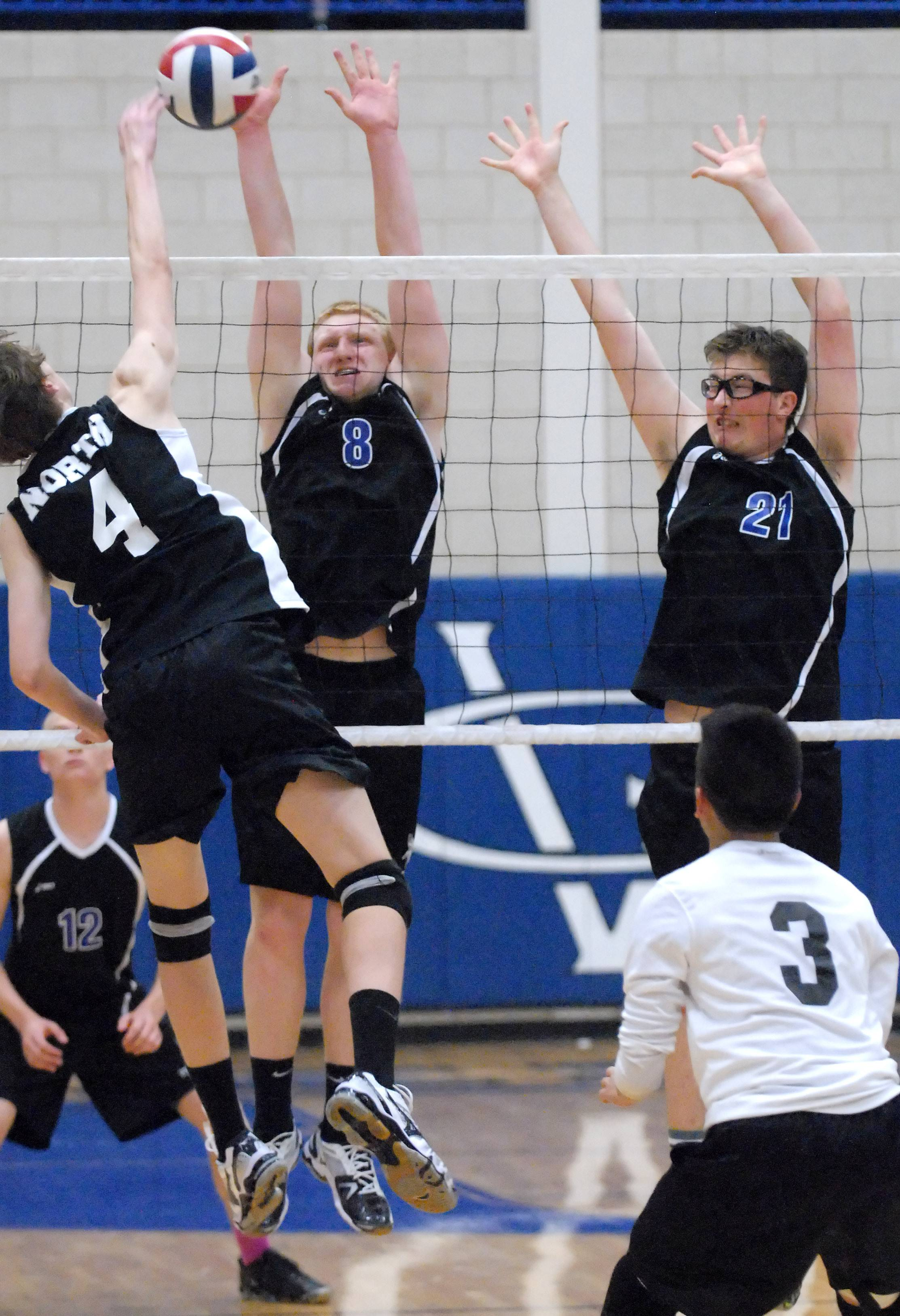 Geneva's Luke Will (8) and Sam Wulfkuhle (21) go for a block against St. Charles North's Drew Lanz in the second game on Tuesday in Geneva.