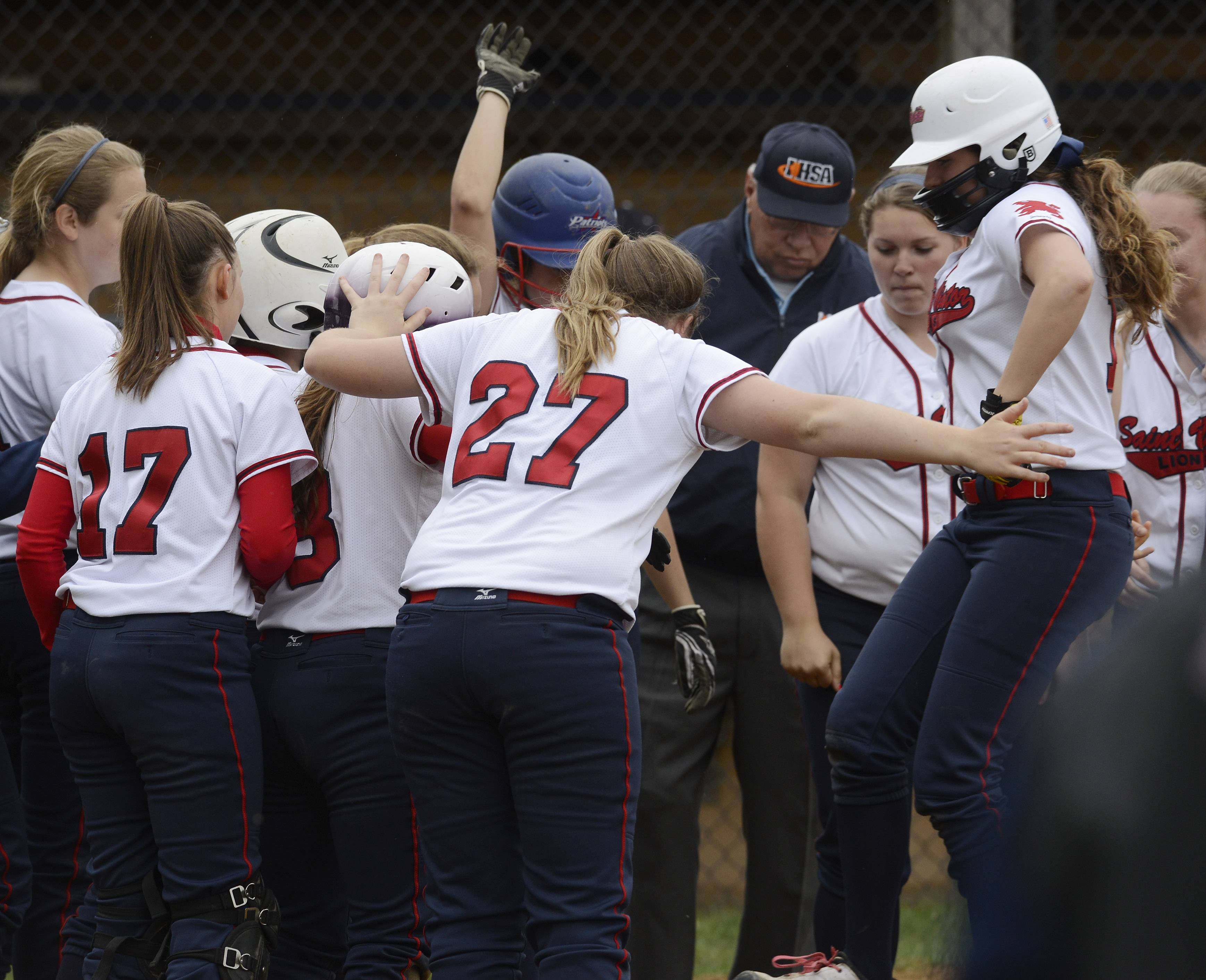 St. Viator's Samantha Hogan is greeted at the plate by her teammates after hitting a 3-run home run against Rolling Meadows during Tuesday's game.