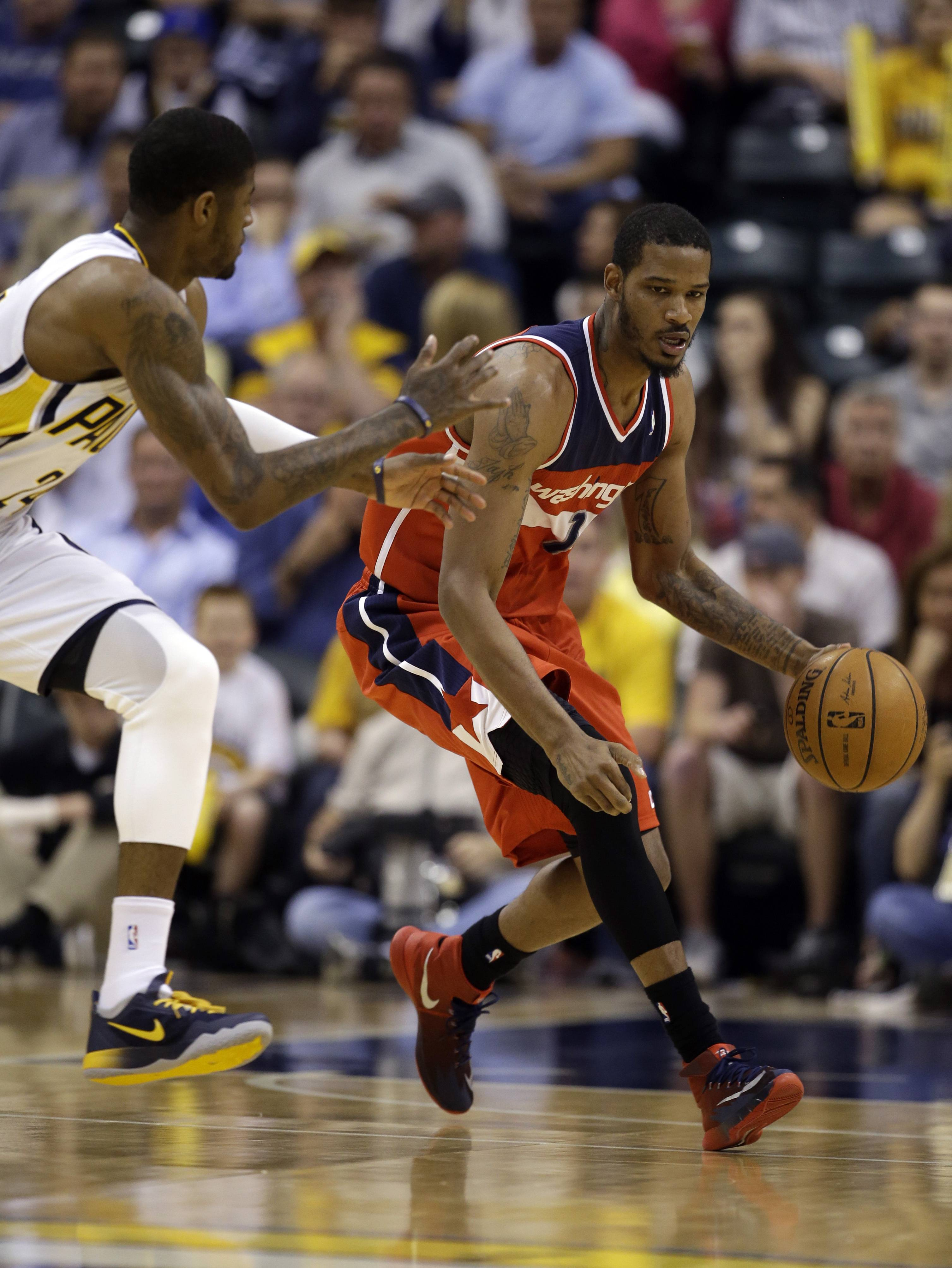 Washington Wizards forward Trevor Ariza, right, drives past Indiana Pacers forward Paul George during the first half of game 5 of the Eastern Conference semifinal NBA basketball playoff series Tuesday, May 13, 2014, in Indianapolis. (AP Photo/Darron Cummings)
