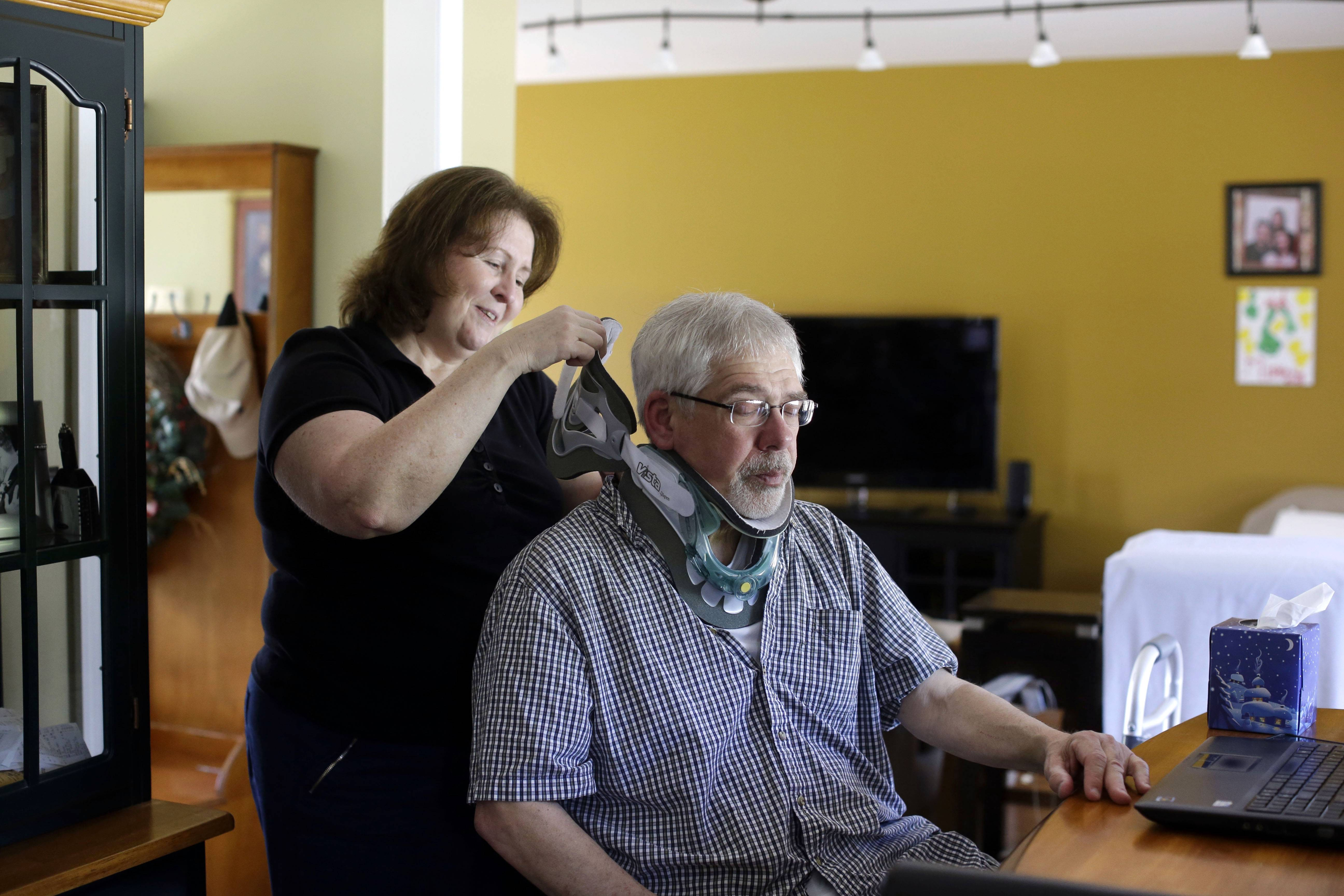 Mark Matulaitis as his wife Colleen helps him with a neck brace that he wears after a recent operation, with his laptop that he uses for virtual house calls with his neurologist in his home in Salisbury, Md.