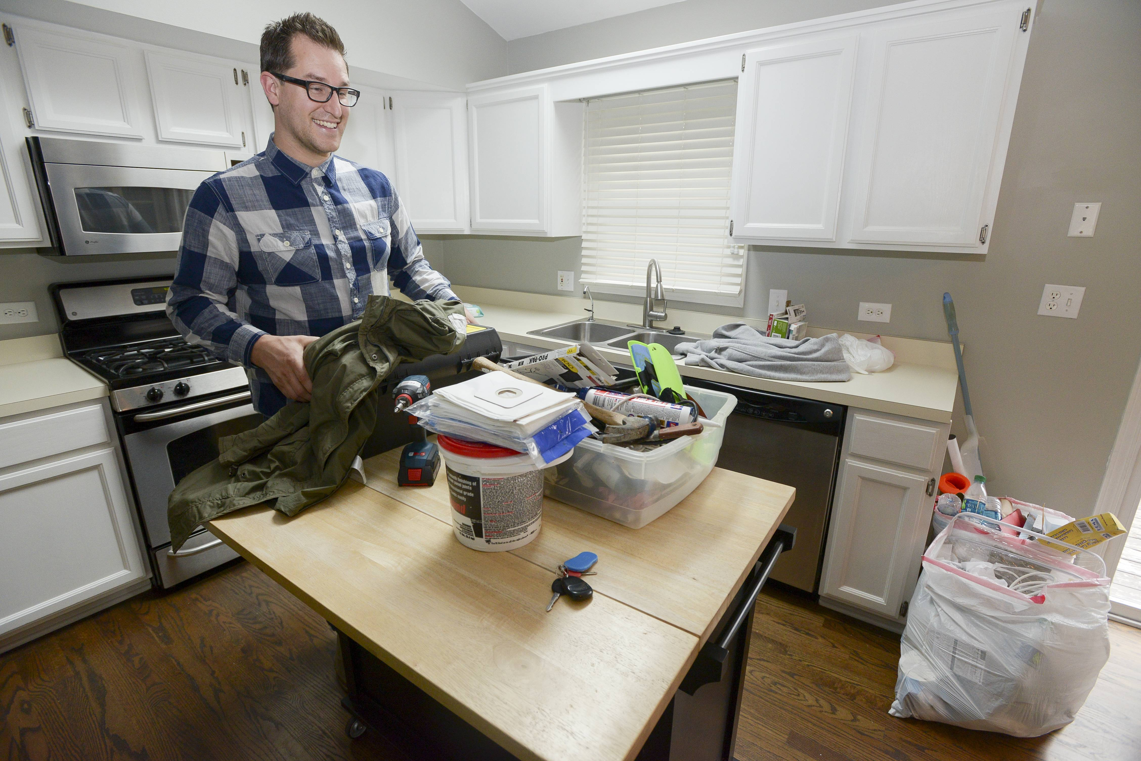 John Hinger picks up a few things left in their empty Warrenville home. The family has sold the house and will spend a month in language and cultural training in Colorado as they prepare for their move to Croatia.
