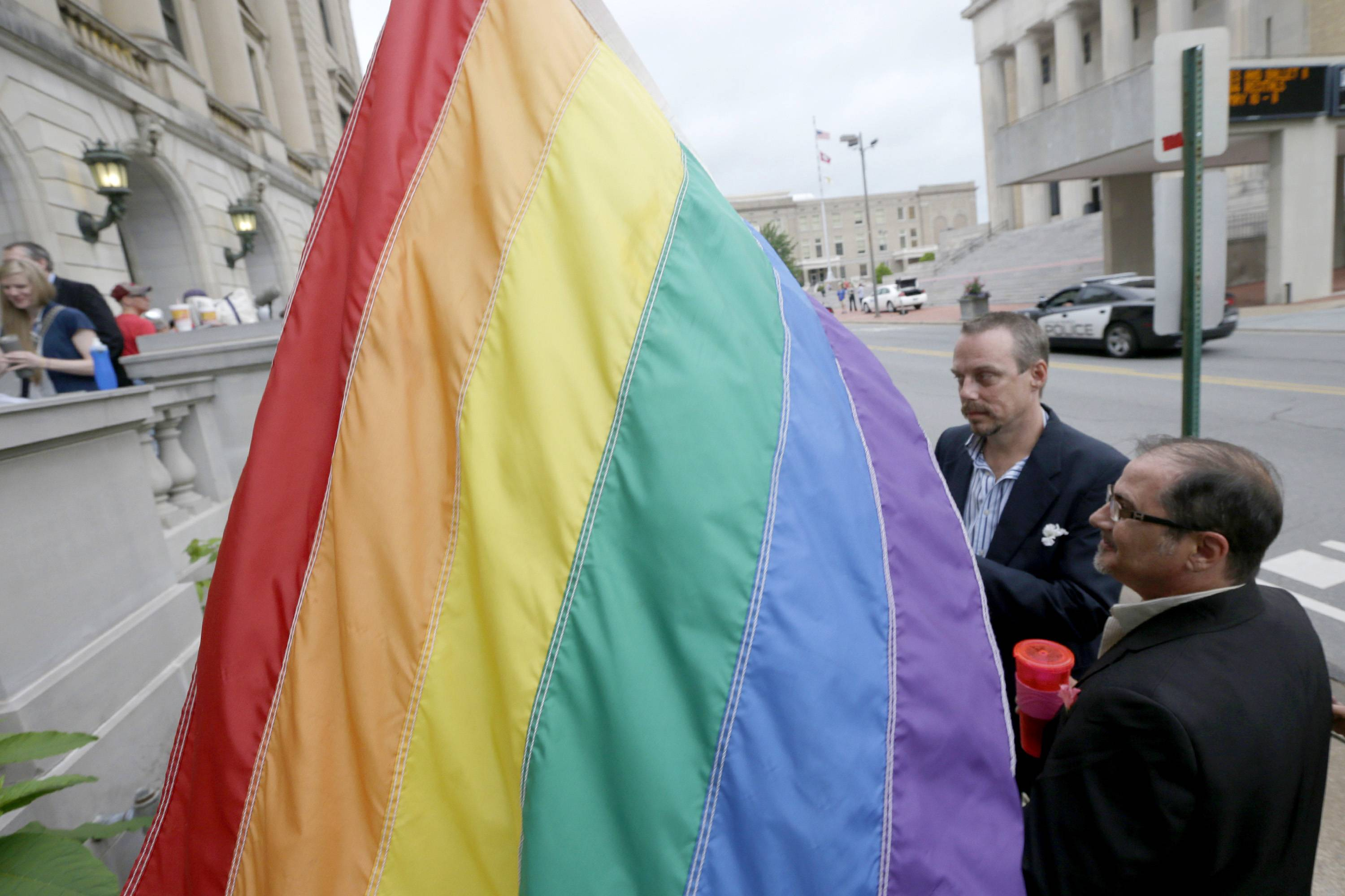 Dozens of Arkansas gay couples, some of whom waited in line overnight, received licenses to marry from county clerks Monday, while lawyers for the state asked its highest court to suspend an order gutting a constitutional amendment that bans same-sex marriage.