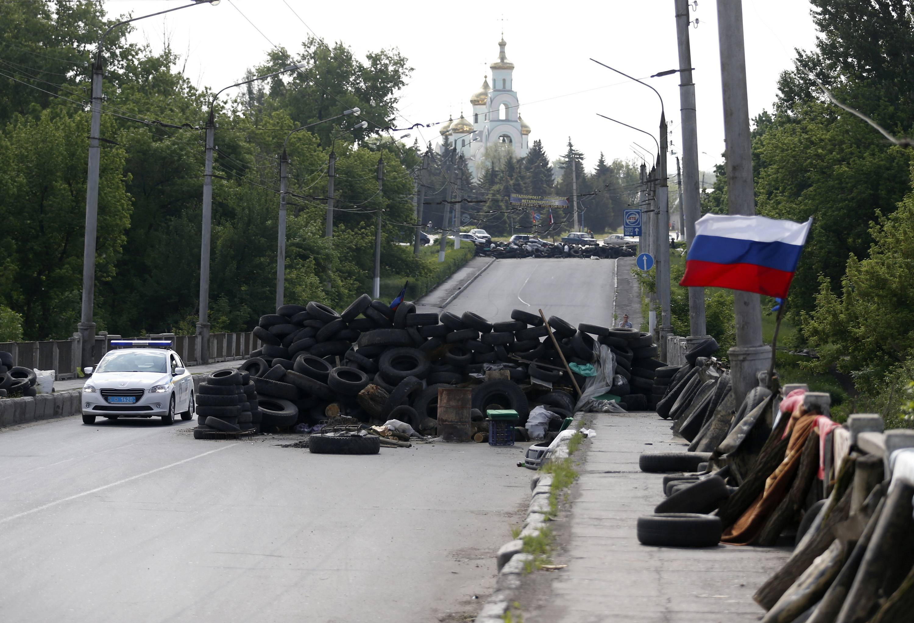 A car passes by the barricades with a Russian national flag on a road leading into Slovyansk, eastern Ukraine, Tuesday, May 13, 2014.