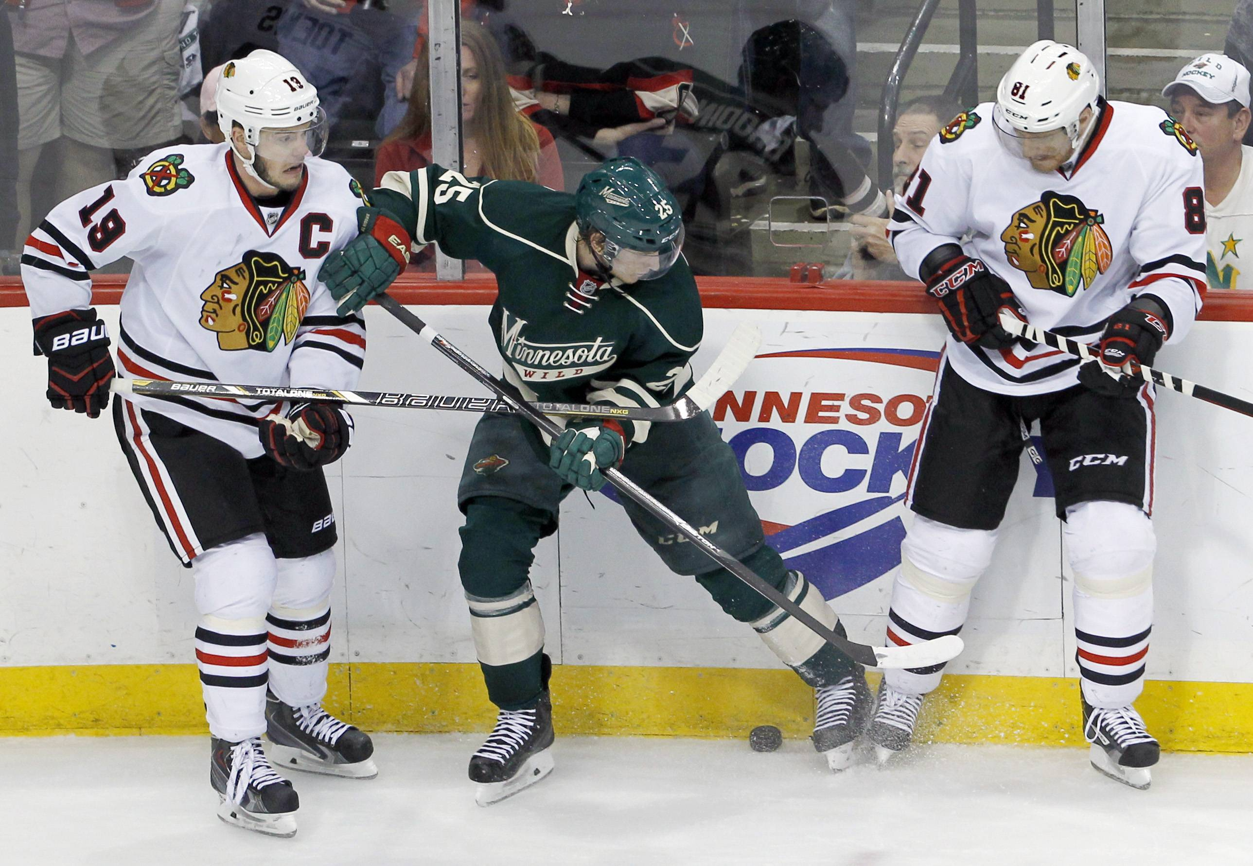 Minnesota Wild defenseman Jonas Brodin (25) is caught between Chicago Blackhawks center Jonathan Toews (19) and Blackhawks right wing Marian Hossa (81), of Czech Republic, as they try to gain control of the puck during the third period .