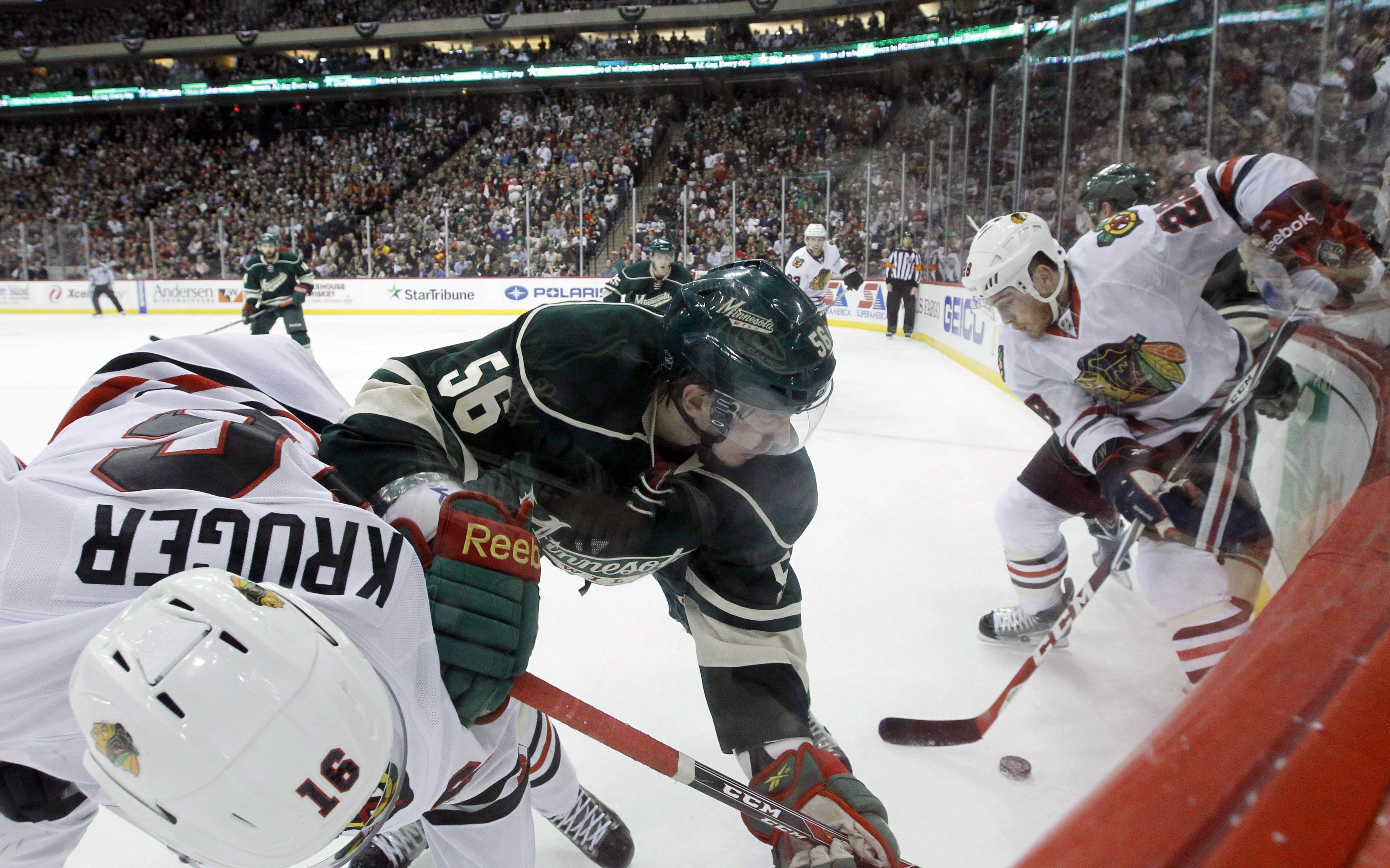 Chicago Blackhawks center Marcus Kruger (16), of Sweden, Minnesota Wild left wing Erik Haula (56), of Finland, and Blackhawks right wing Ben Smith (28) chase the puck during the second period.