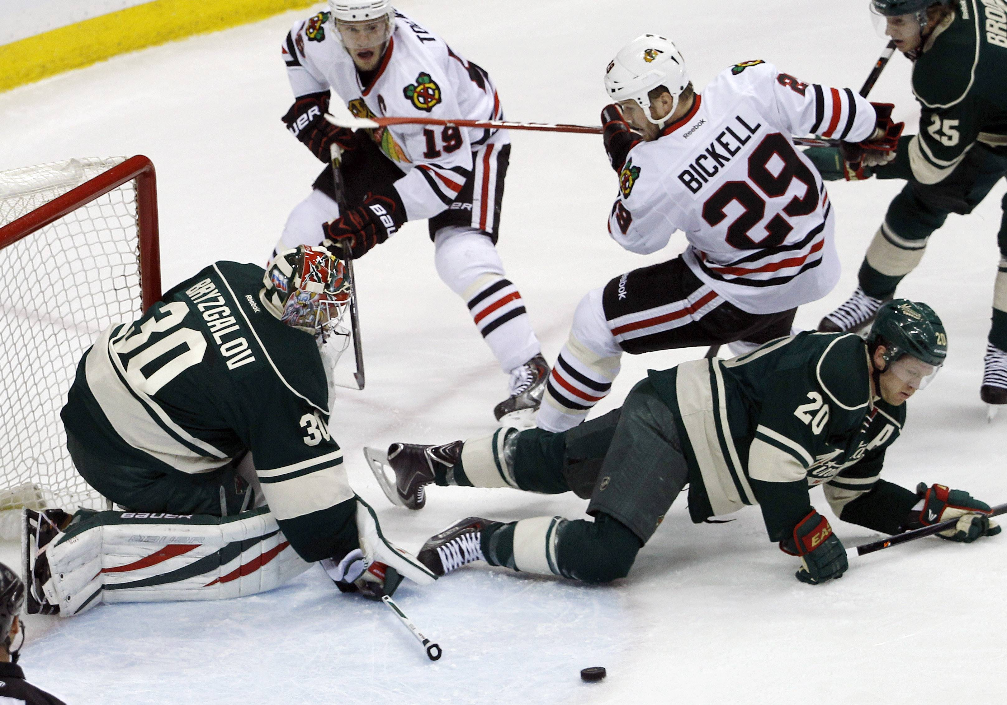 Chicago Blackhawks left wing Bryan Bickell (29) lands on Minnesota Wild defenseman Ryan Suter (20) as Wild goalie Ilya Bryzgalov (30), of Russia, deflects a shot during the first period .