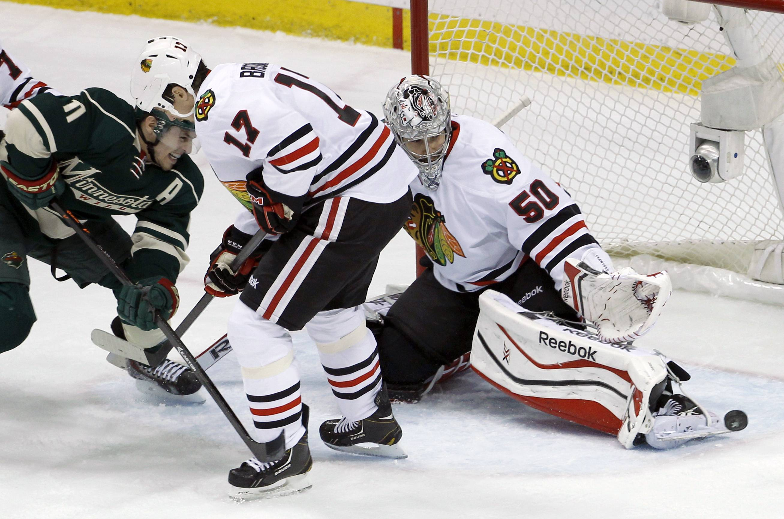 Chicago Blackhawks goalie Corey Crawford (50) deflects a shot in front of  Blackhawks defenseman Sheldon Brookbank (17) and Minnesota Wild left wing Zach Parise (11) during the first period.