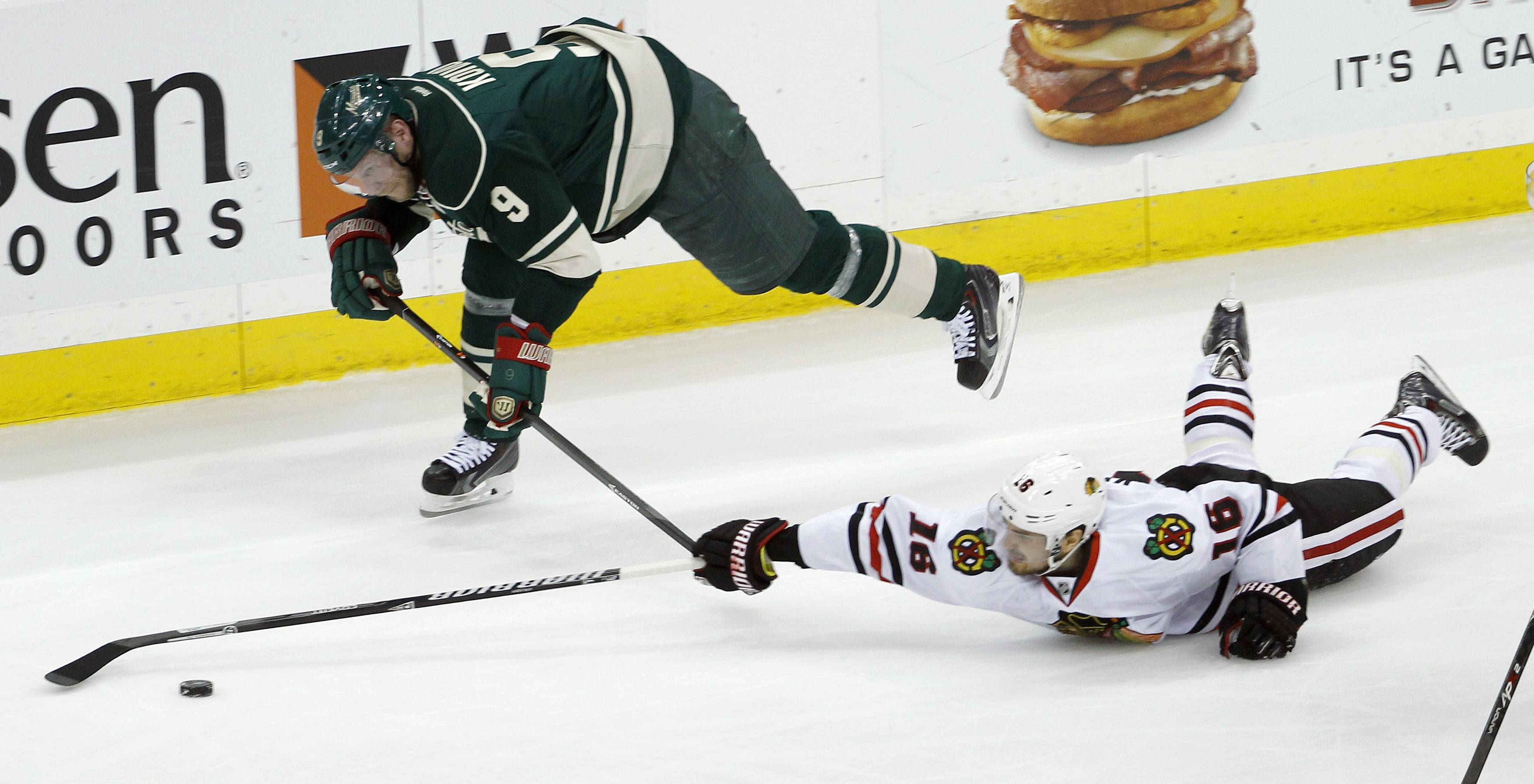 Minnesota Wild center Mikko Koivu (9), of Finland, and Chicago Blackhawks center Marcus Kruger (16), of Sweden, chase the puck during the first period.