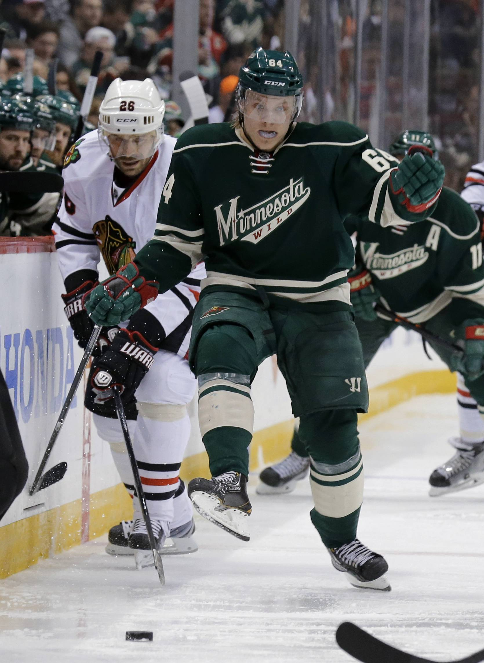 Minnesota Wild center Mikael Granlund (64), of Finland, kicks the puck to a teammate in front of Chicago Blackhawks center Michal Handzus (26), of the Czech Republic, during the second period.