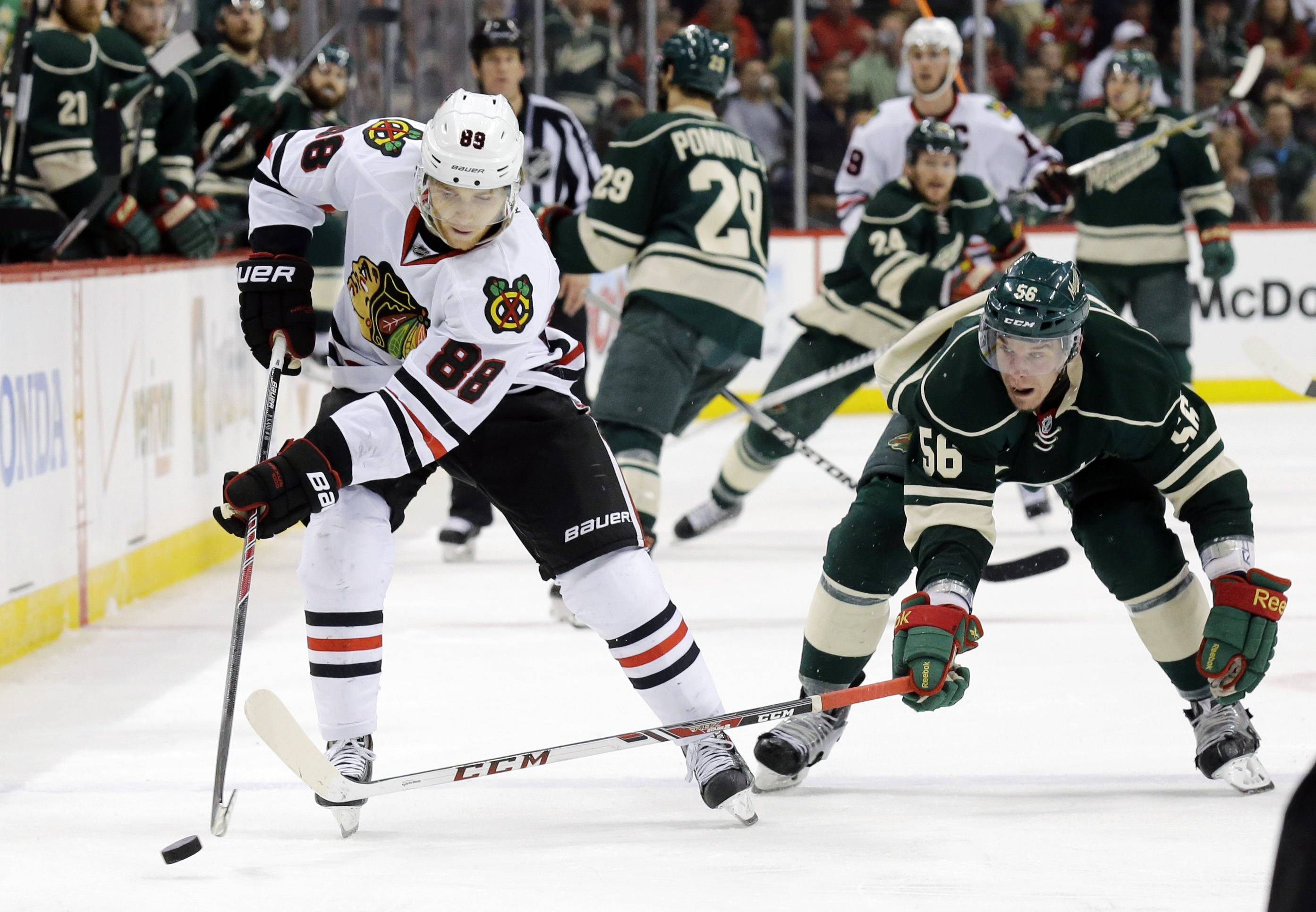 Chicago Blackhawks right wing Patrick Kane (88) and Minnesota Wild left wing Erik Haula (56), of Finland, chase the puck during the second period.