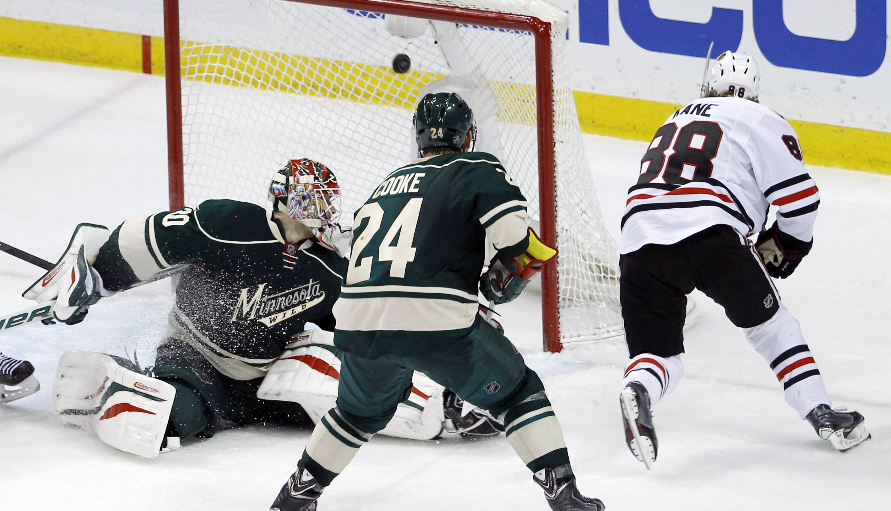 The game-winning shot by Chicago Blackhawks right wing Patrick Kane (88) gets past Minnesota Wild goalie Ilya Bryzgalov, left, of Russia, in front of Wild left wing Matt Cooke (24) during overtime.