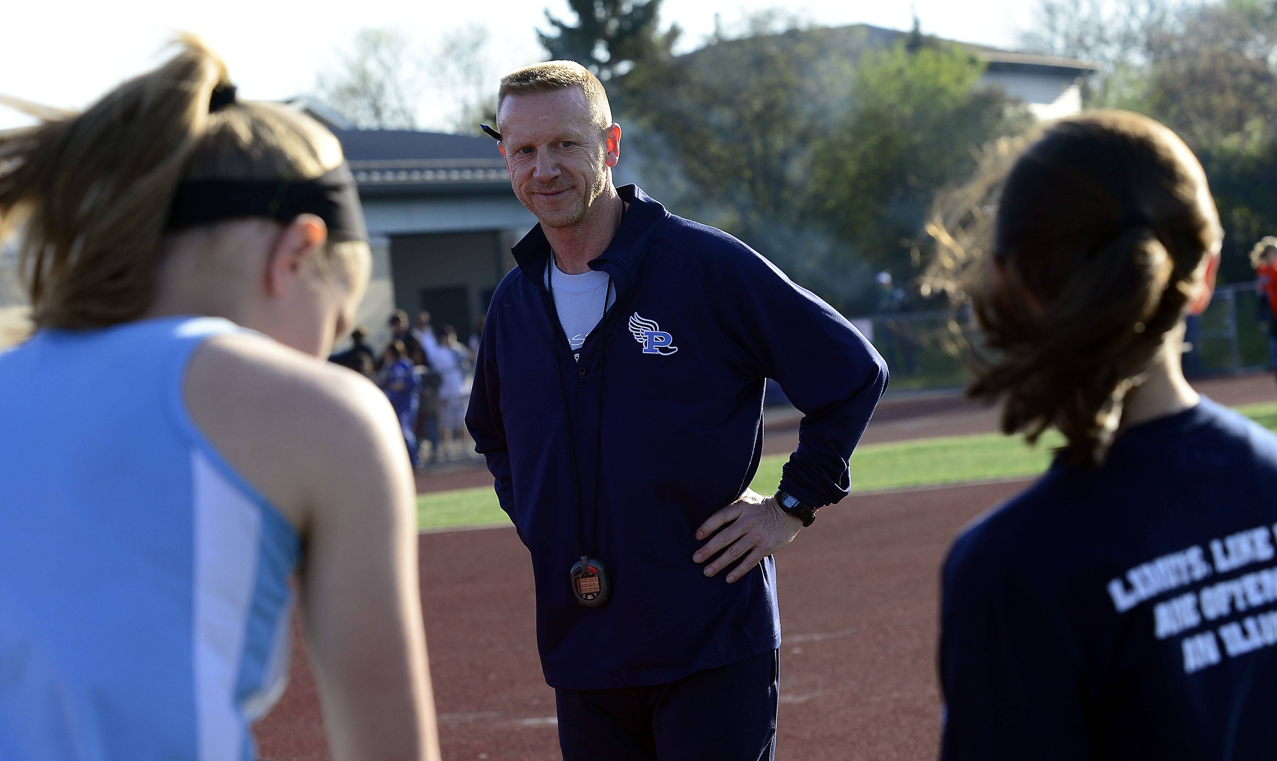 Prospect's girls track and field coach Dave Wurster works with his athletes during his final Mid-Suburban League meet last weekend at Wheeling.