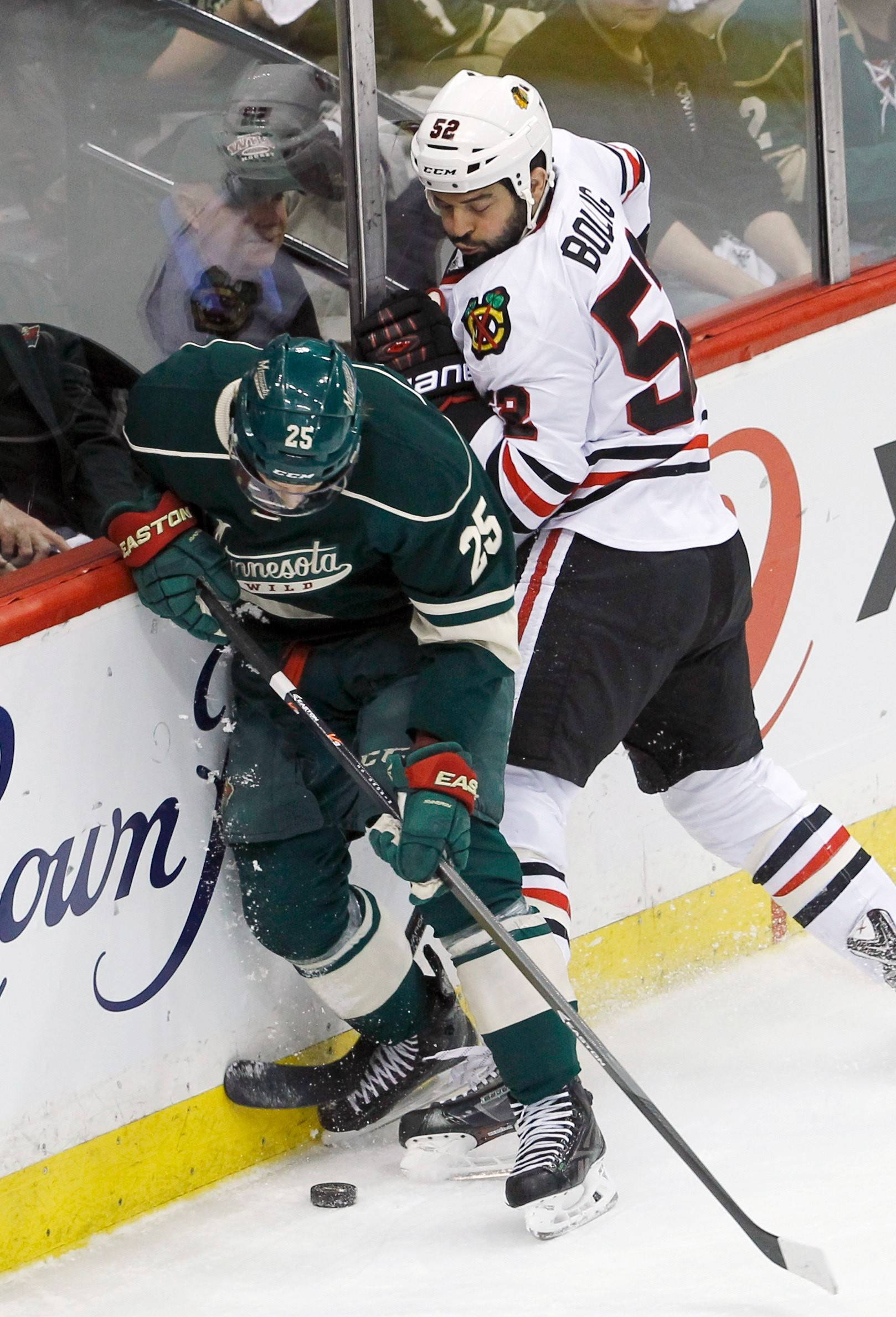 Minnesota Wild defenseman Jonas Brodin (25) and Chicago Blackhawks left wing Brandon Bollig (52) battle for the puck during the first period of Game 3 of an NHL hockey second-round playoff series in St. Paul, Minn., Tuesday, May 6, 2014.