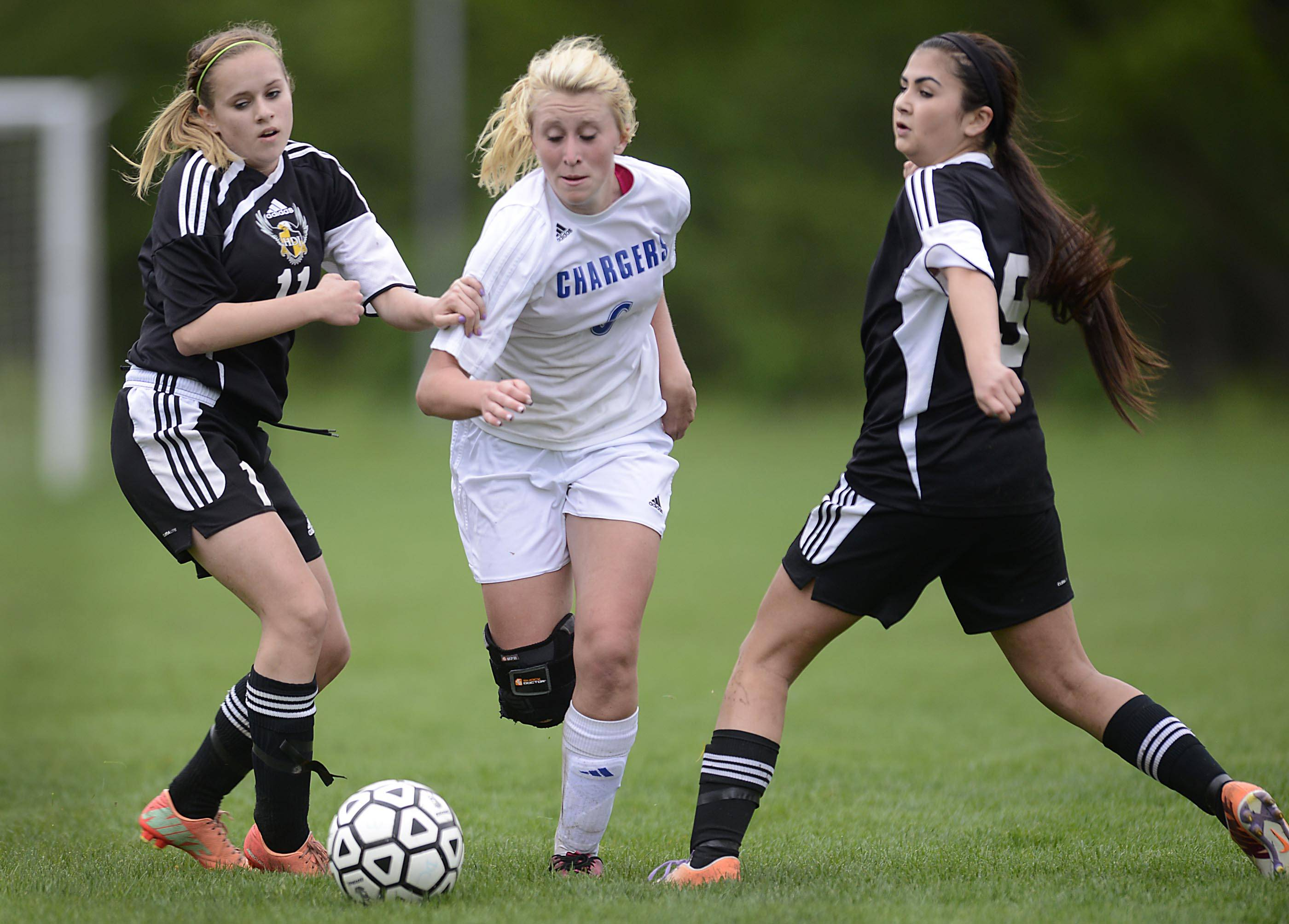 Dundee-Crown's Shannon Feld dribbles between the defense of Jacobs' Kyra Blankenship and Amanda Pasetes, right, Tuesday in Carpentersville.