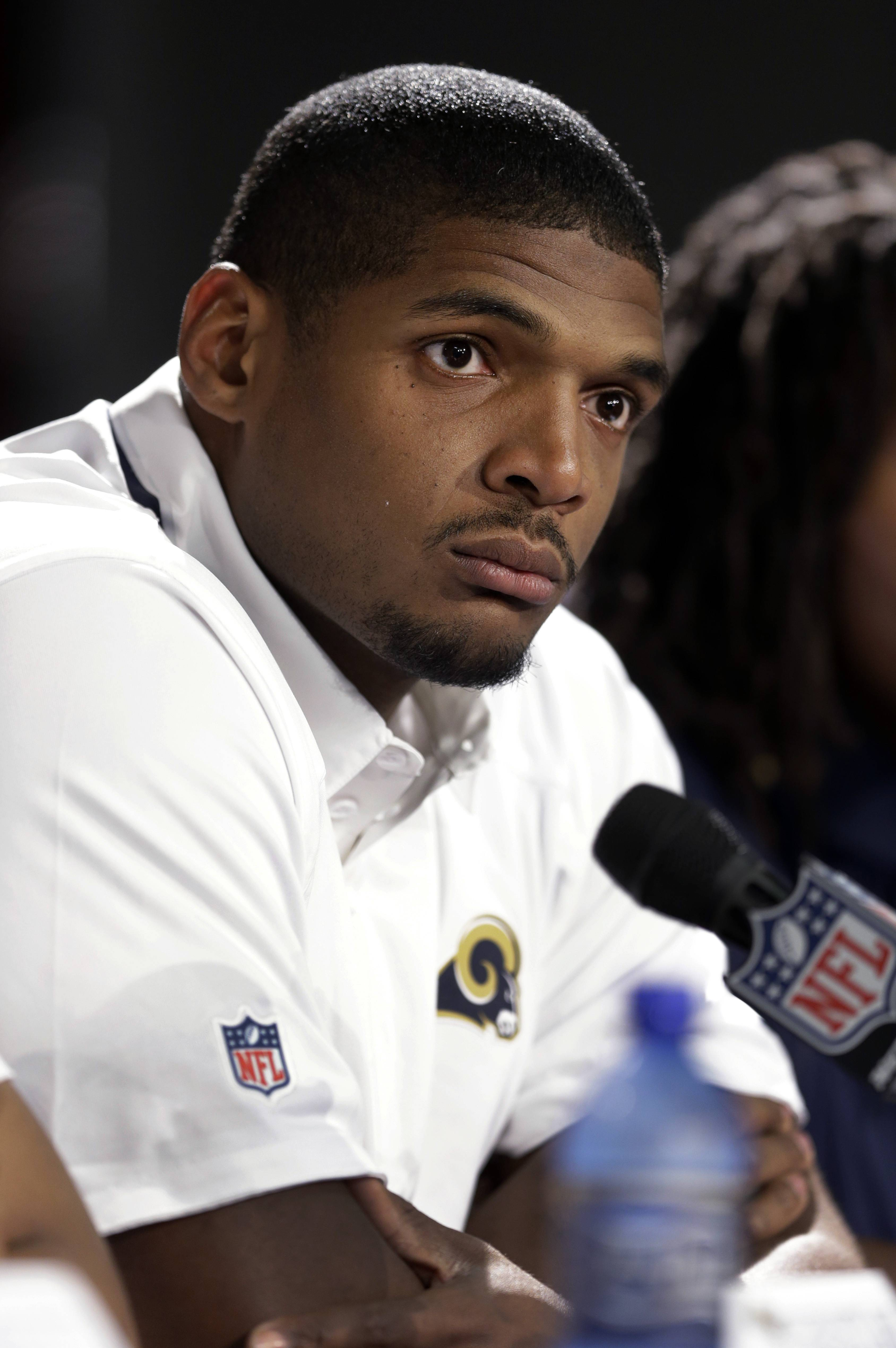 St. Louis Rams seventh-round draft pick Michael Sam listens to a question during a news conference at the NFL football team's practice facility Tuesday, May 13, 2014, in St. Louis.