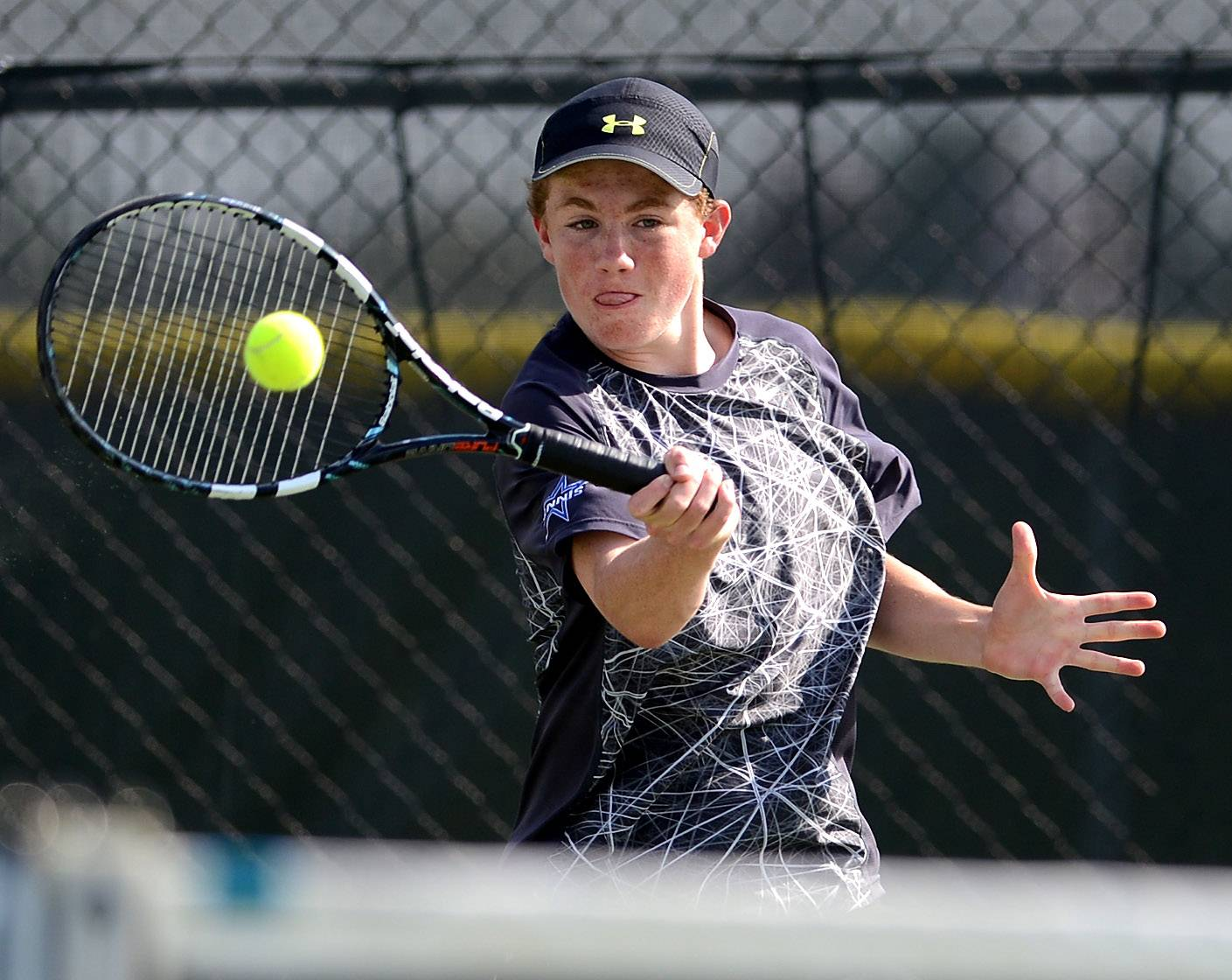 Matt Ernst of St. Charles North returns a serve in a #1 singles match against Tim Murat of Batavia on Thursday.