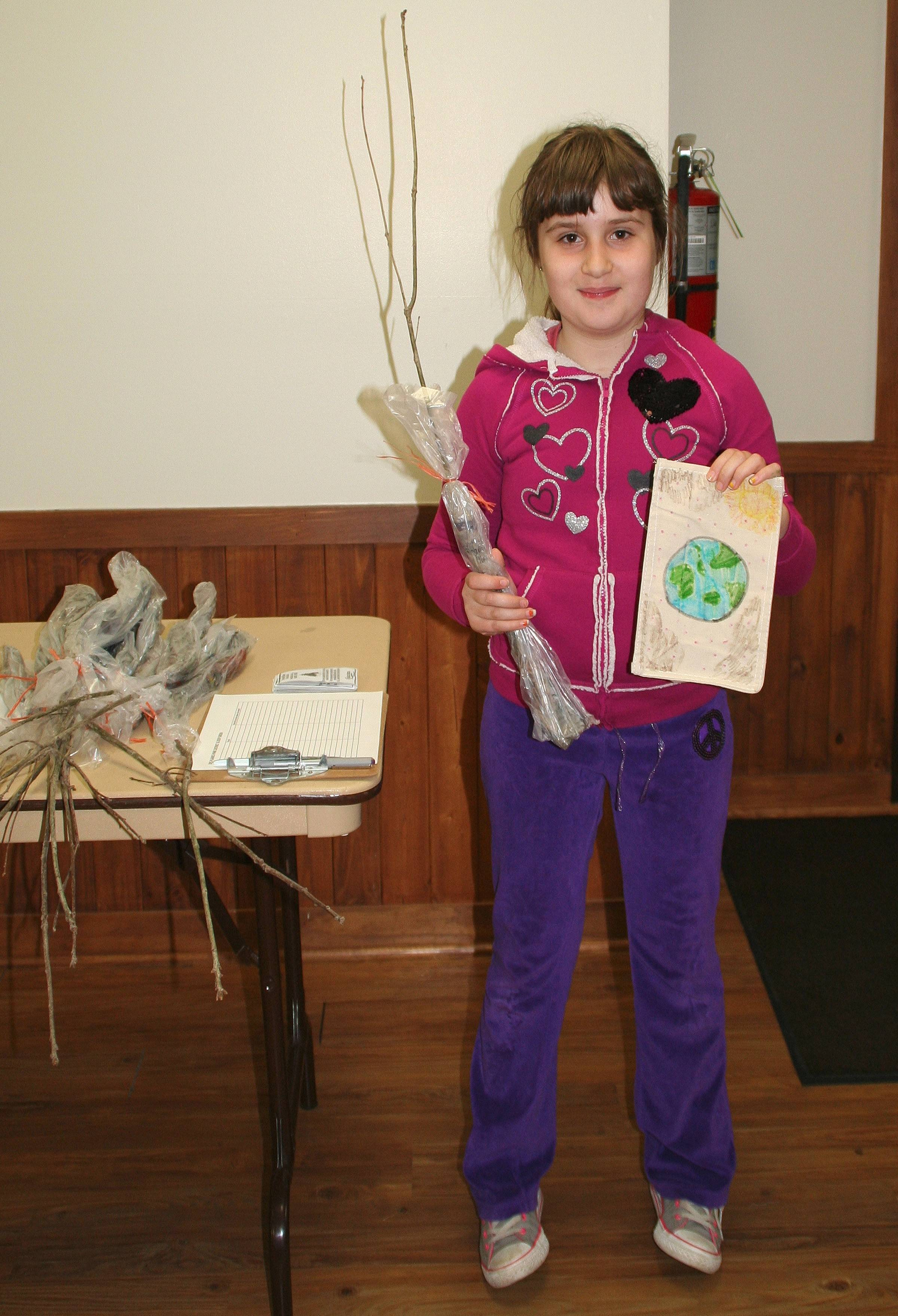 Maddie Chiakas, 10, chooses a free oak sapling at the Earth Day Youth Fair on April 26.