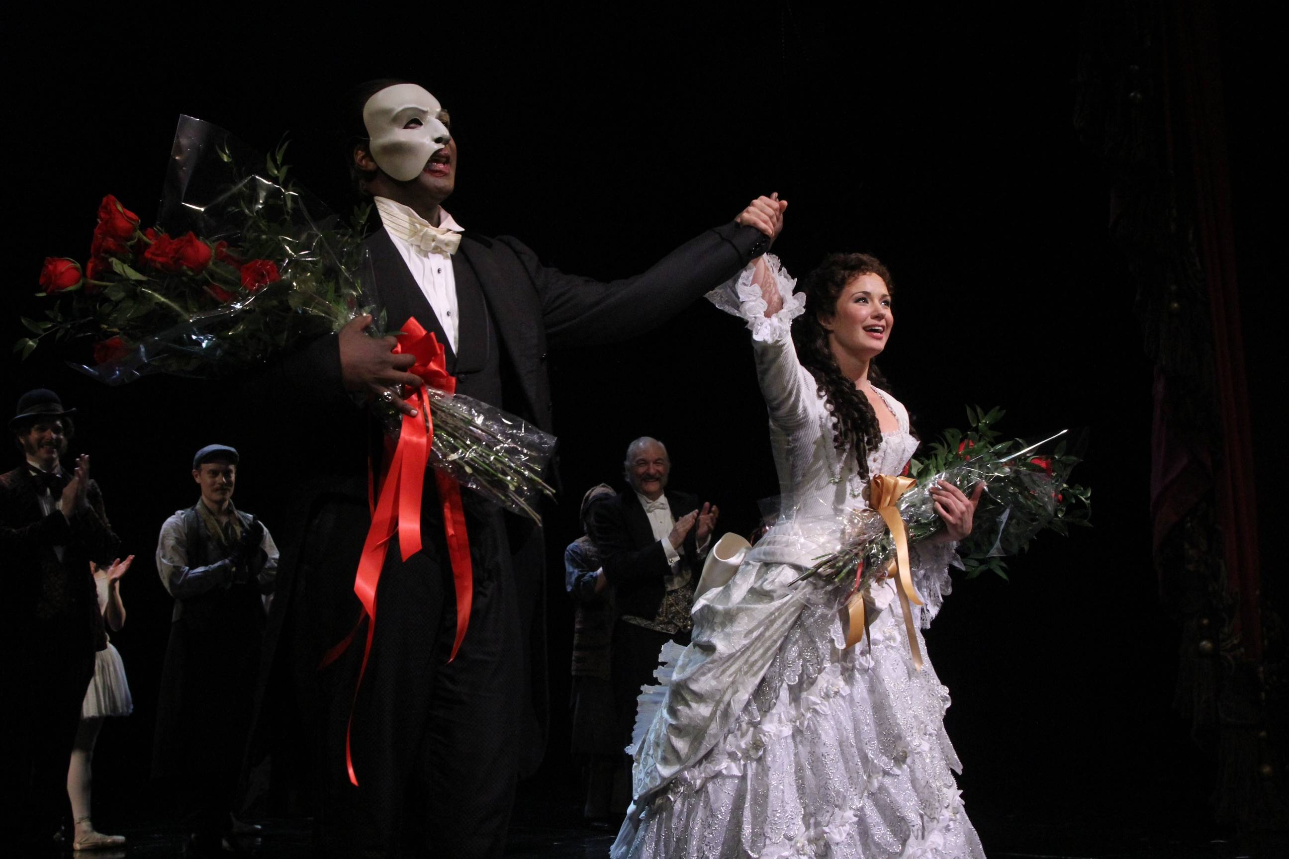 "This May 12, 2014 photo released by The Publicity Office shows Norm Lewis, left, and Sierra Boggess acknowledging applause on the pair's opening night with the Broadway production of The Phantom of the Opera at The Majestic Theatre, in New York. Lewis is the first African-American actor to take on the title role in Broadway's ""The Phantom of the Opera."" (AP Photo/The Publicity Office, Bruce Glikas)"