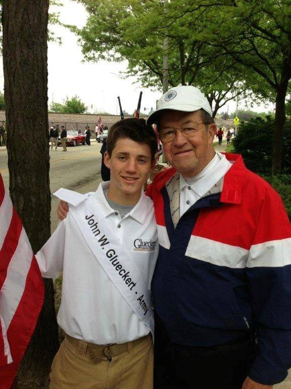Riley Glueckert marches with his grandfather John W. Glueckert, an Army veteran, during the honor flag processional in the 2013 Arlington Heights Memorial Day Parade.