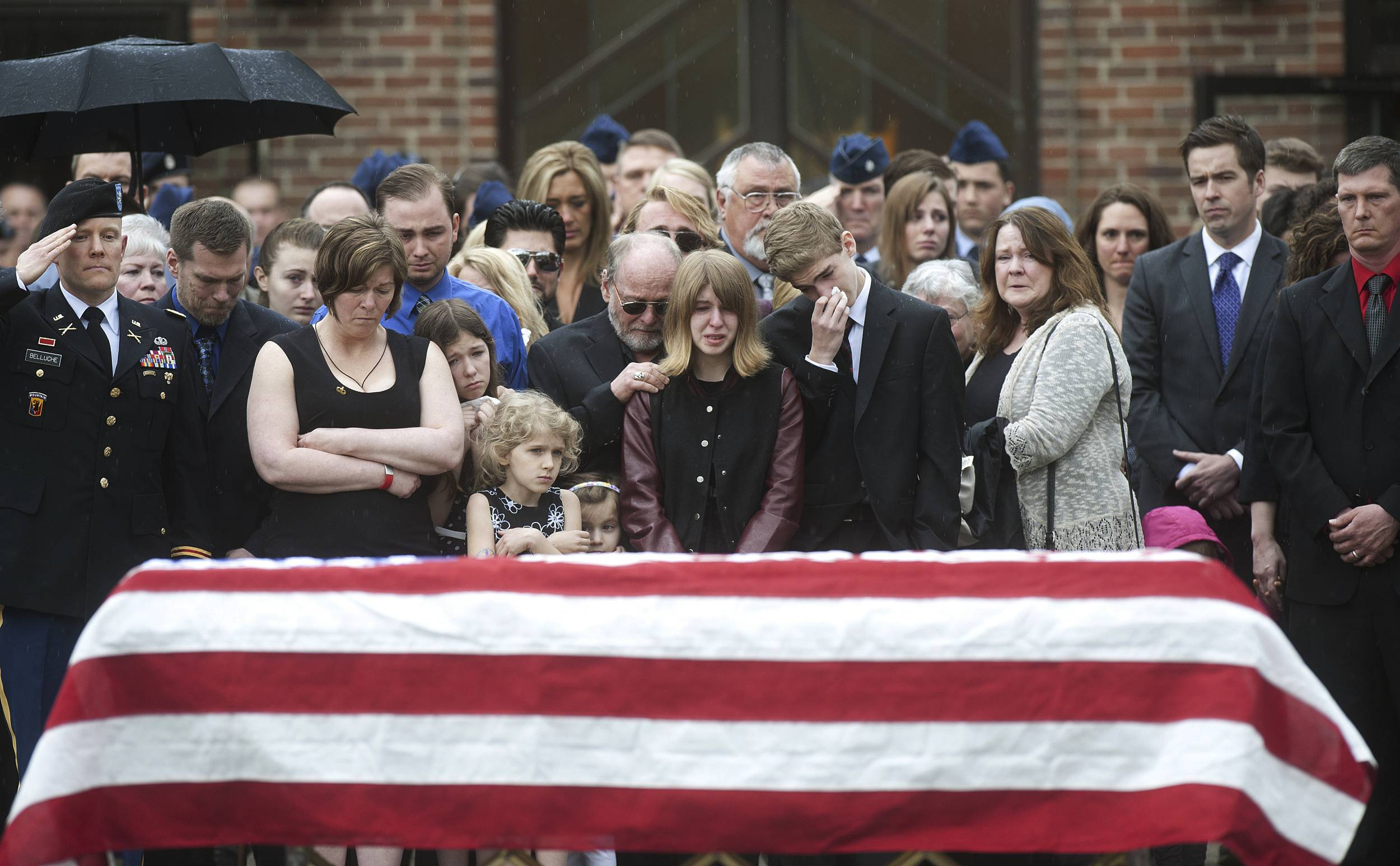 Family, friends and members of the military gather beside Kryn Miner's casket after his funeral. His widow, Amy Miner, third from left, believes the Veterans Affairs health system must do more to help veterans who struggle with PTSD after returning home.