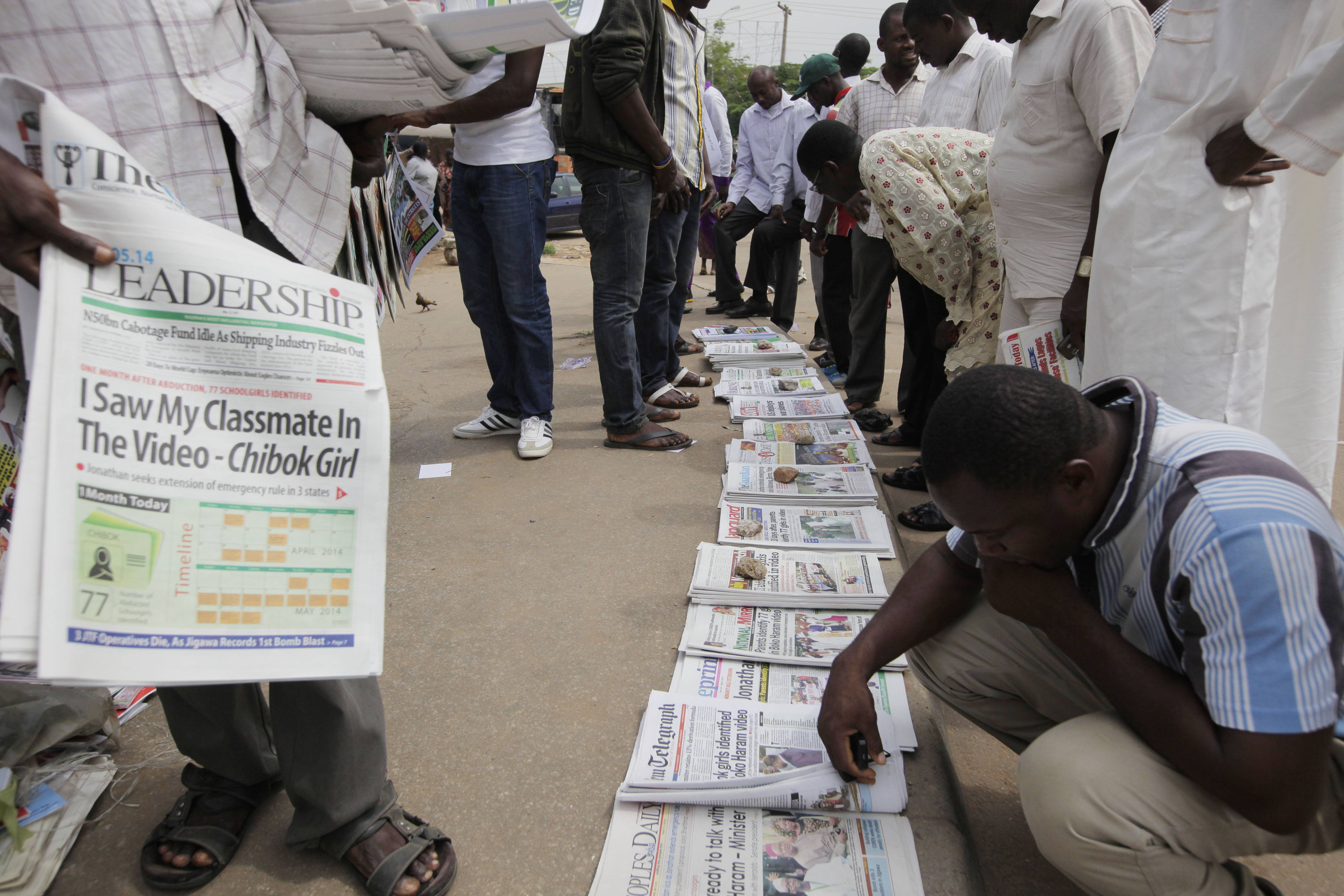 People read newspapers with headlines stating, 'I saw my classmate in the video,' referring to the kidnapped schoolgirls of a government secondary school Chibok, in a video released on Monday by Boko haram, in Abuja, Nigeria, Wednesday.