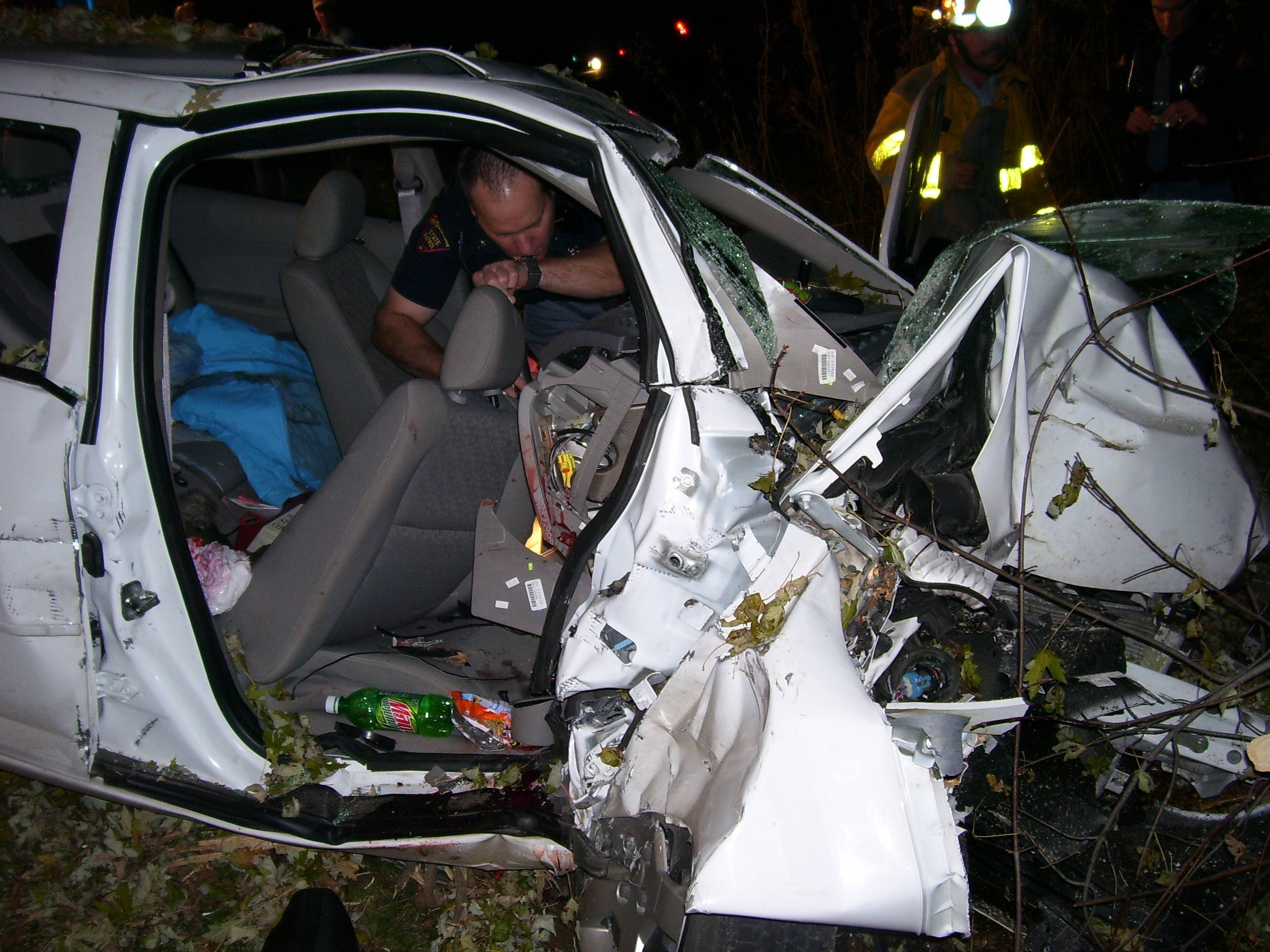 "In this Oct. 24, 2006 photo provided by the St. Croix County Sheriff's Office, police investigate the wreckage of a 2005 Chevrolet Cobalt that crashed in St. Croix County, killing two and injuring one. The vehicle's ignition was found in the ""accessory"" position and the air bags didn't deploy."