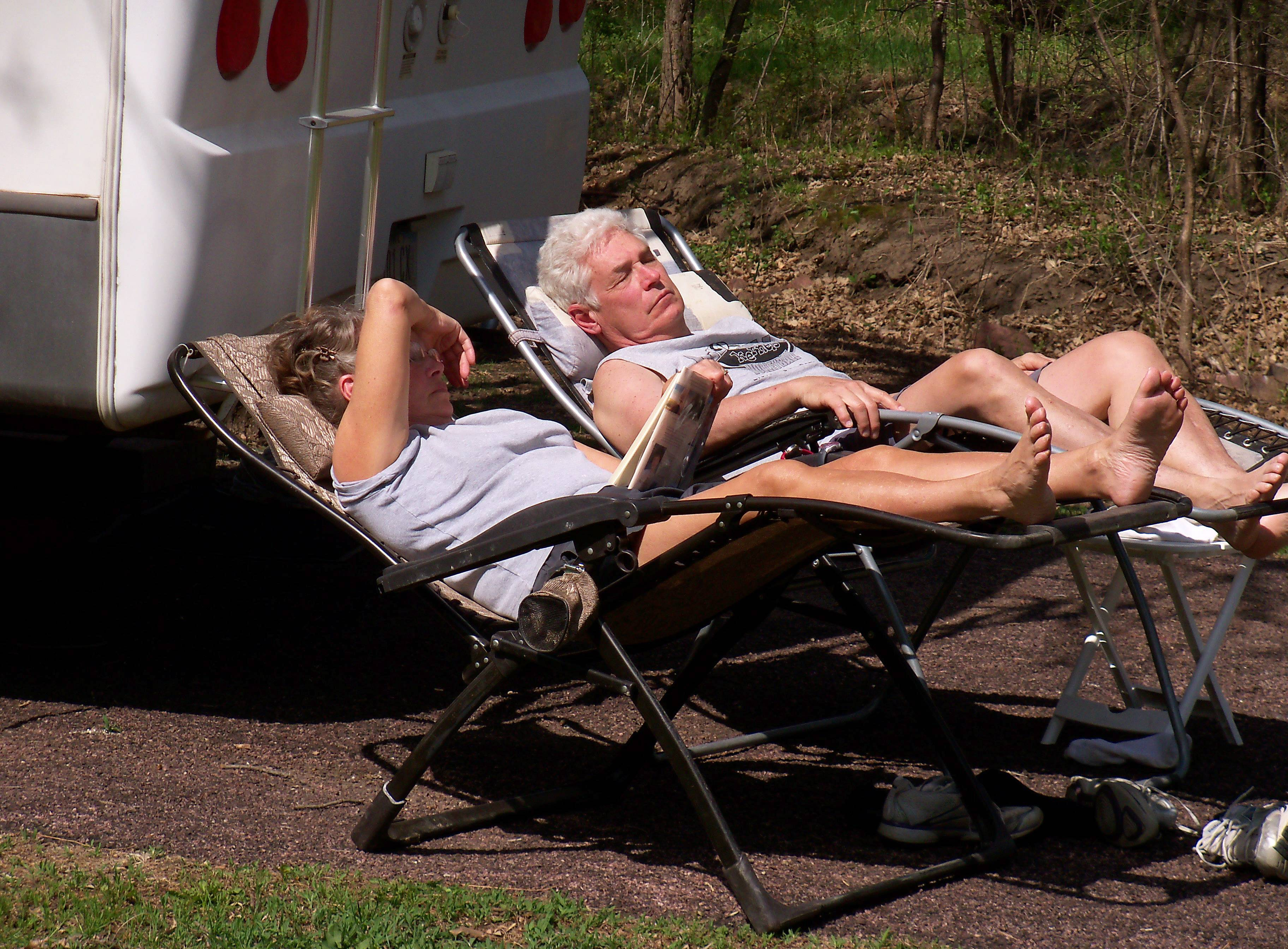 Patricia Zwart of Larchwood, Iowa, reads a book while her husband relaxes next to their camper in Palisades State Park in South Dakota near the Minnesota border. The Zwarts are among a number of Americans enjoying early season camping after a brutal winter.