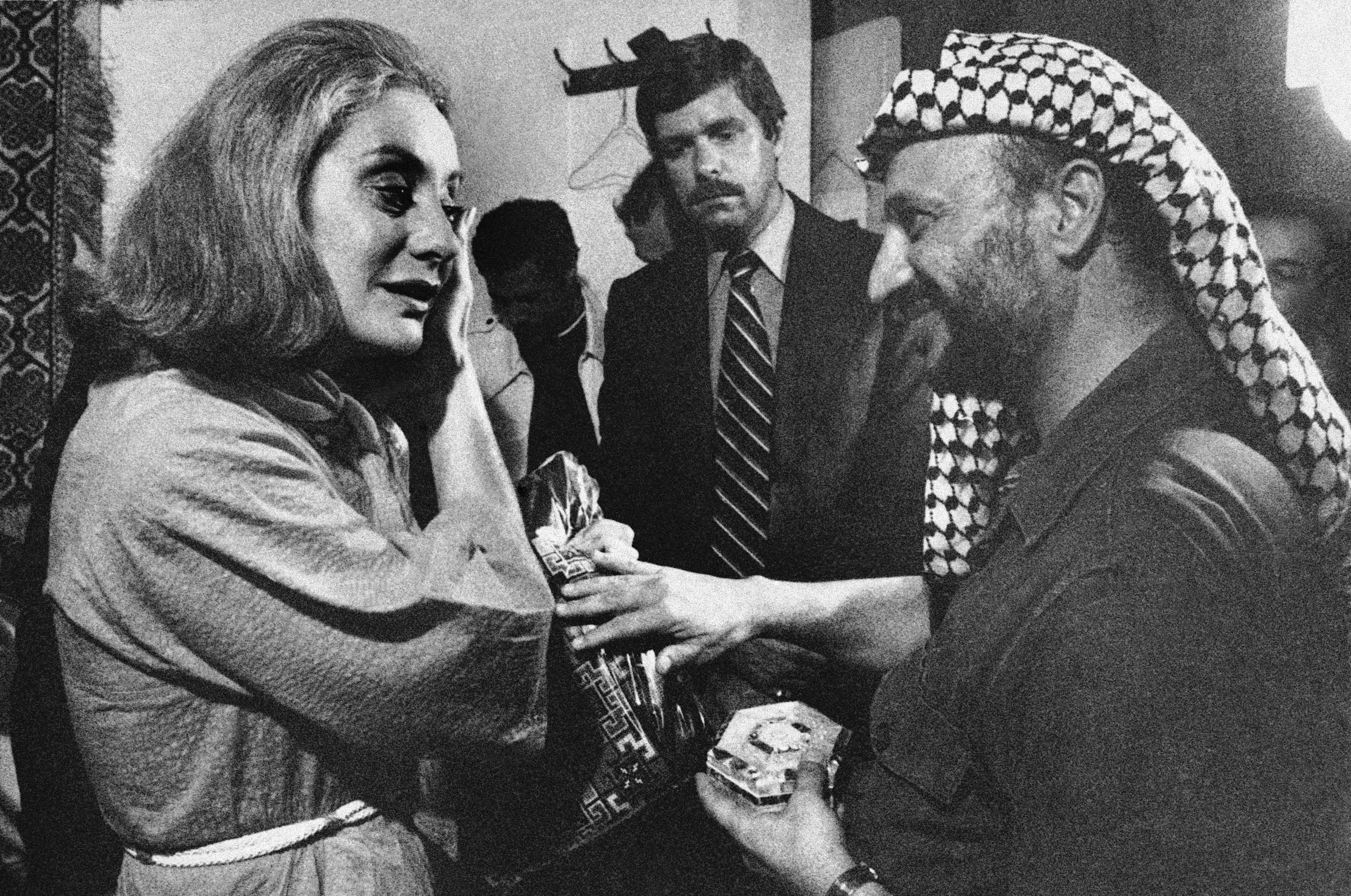Palestinian leader Yasser Arafat, right, presented ABC's Barbara Walters with a handmade dress and mother-of-pearl box following an interview with him in Beirut on Sept. 21, 1977.