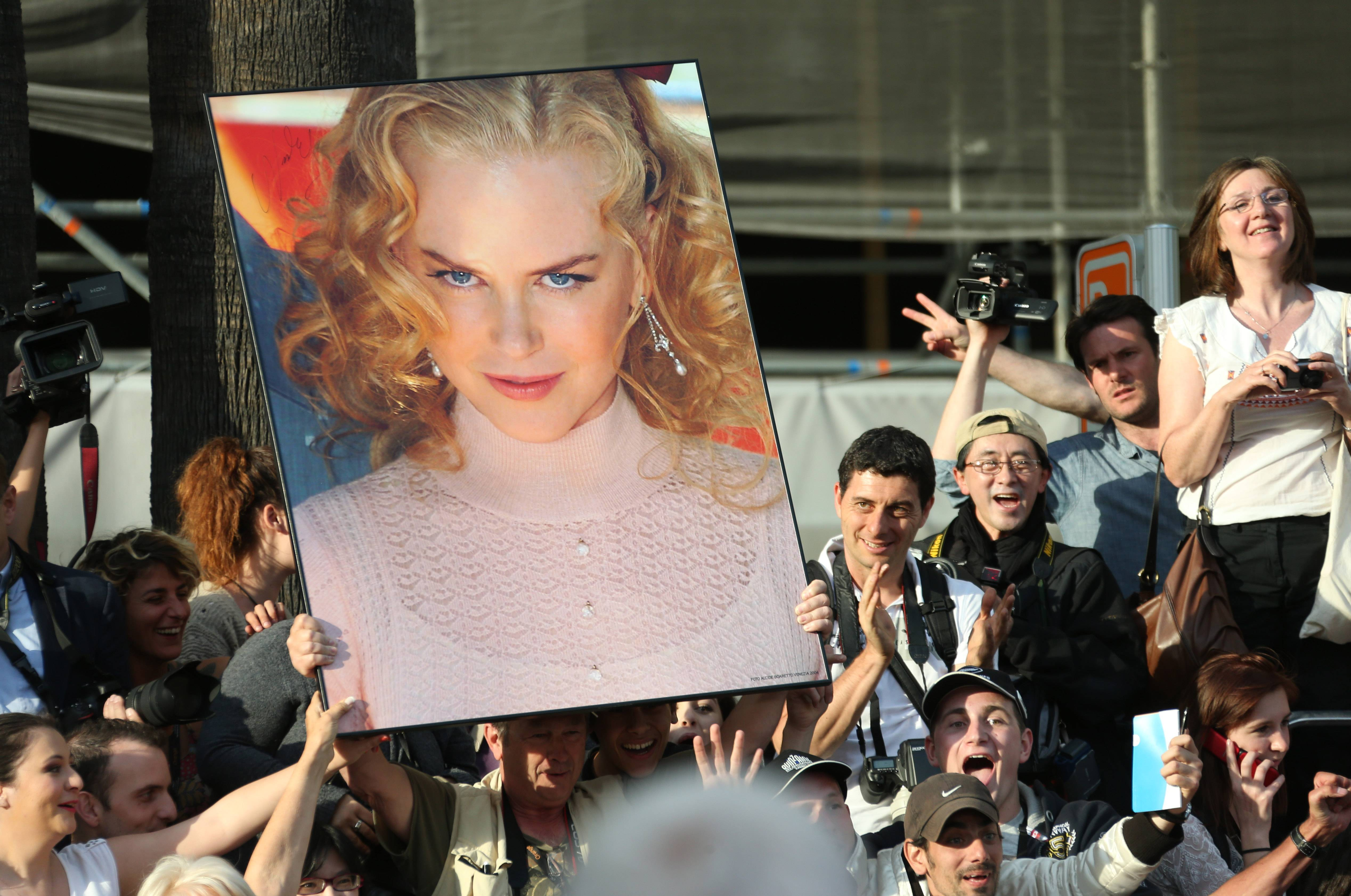 "Fans hold up a giant poster of actress Nicole Kidman as they await arrivals Wednesday for the opening ceremony and the screening of ""Grace of Monaco"" at the 67th Cannes Film Festival in southern France."