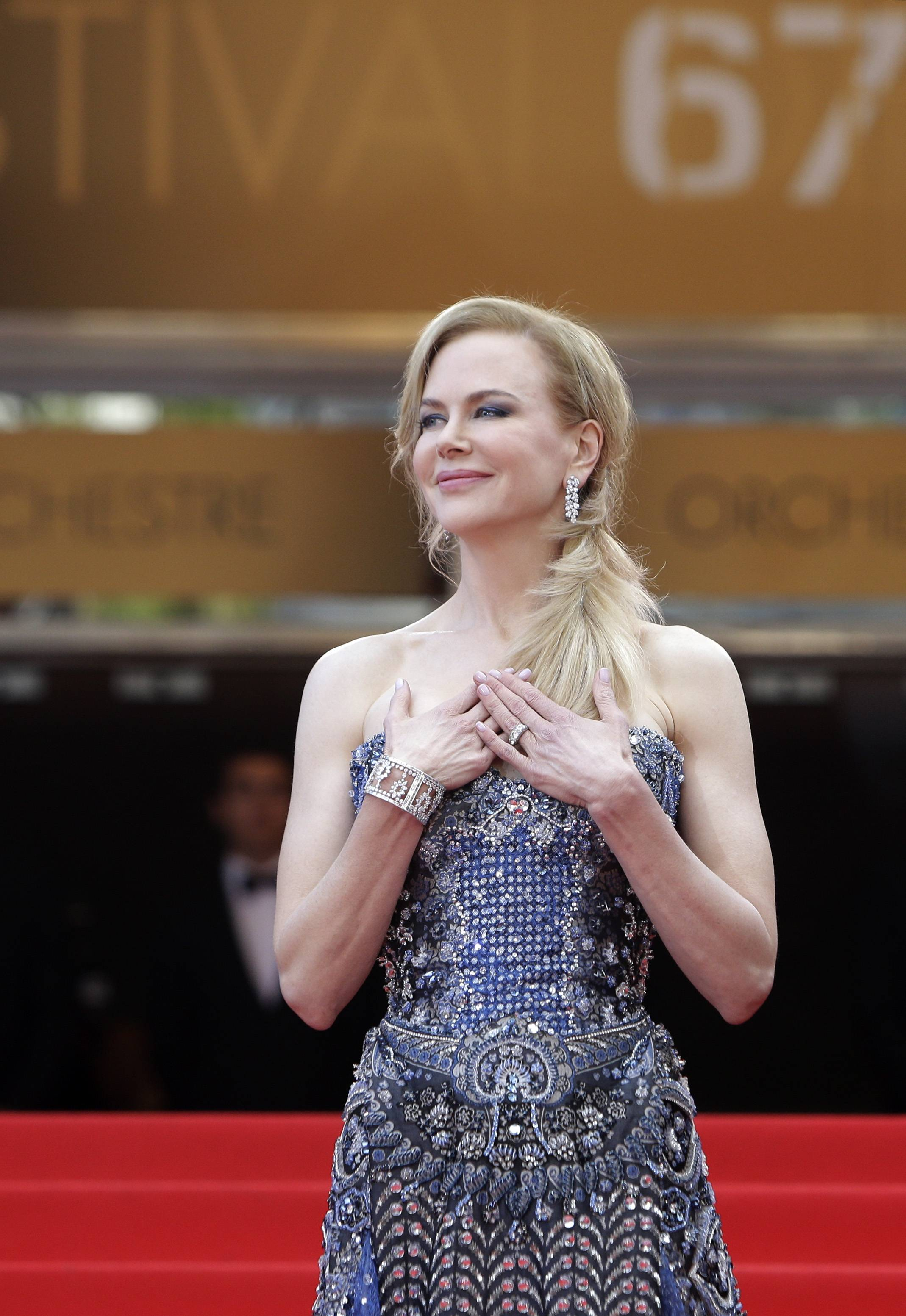 "Actress Nicole Kidman stands at the top of the red carpet Wednesday as she arrives for the opening ceremony and screening of ""Grace of Monaco"" at the 67th Cannes Film Festival in southern France."